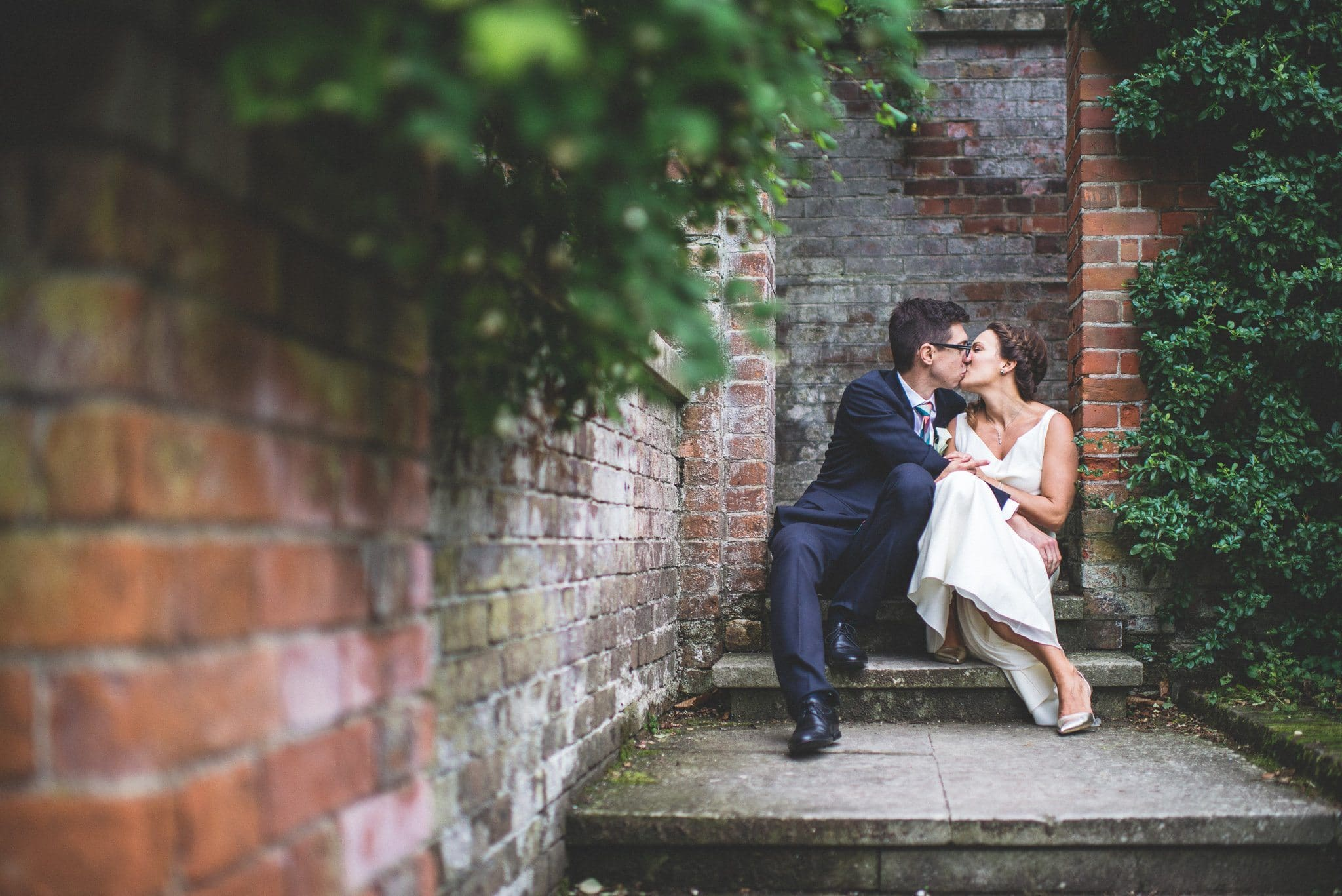 The newlyweds kiss against a backdrop of red brick and dark green foliage