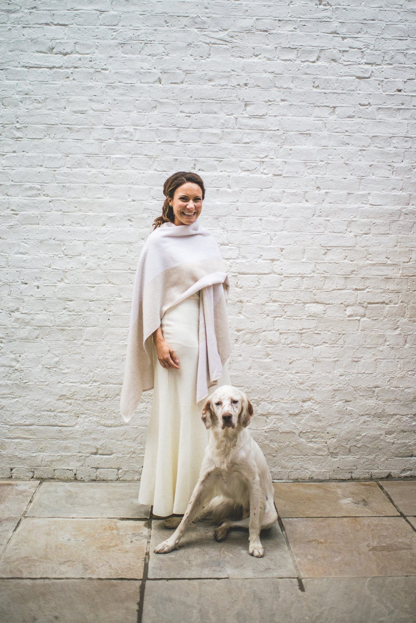 Ilaria poses with her dog. She is wrapped up against the cold in a cashmere shawl.
