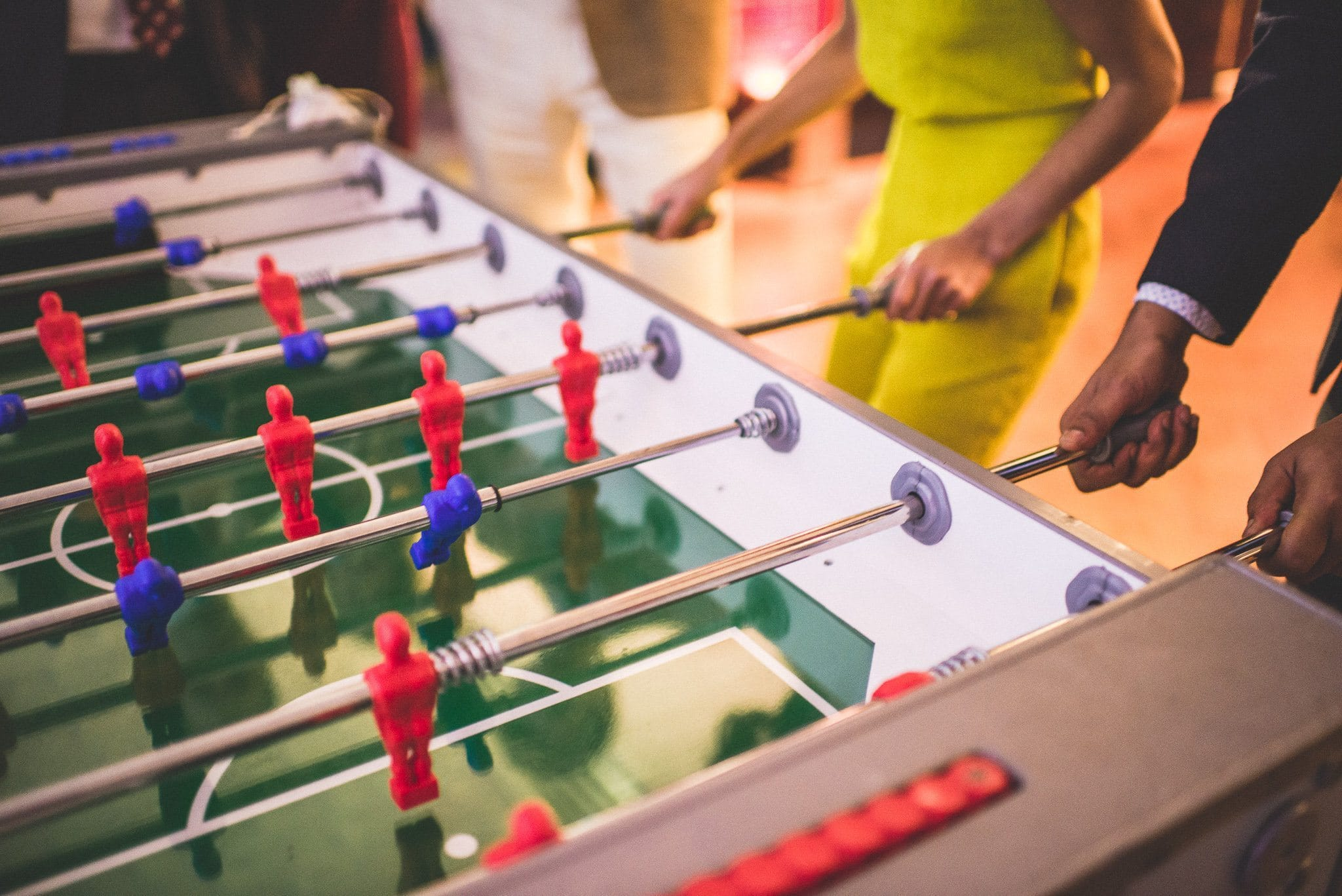 A close up of a cut-throat table football match being played at the reception venue