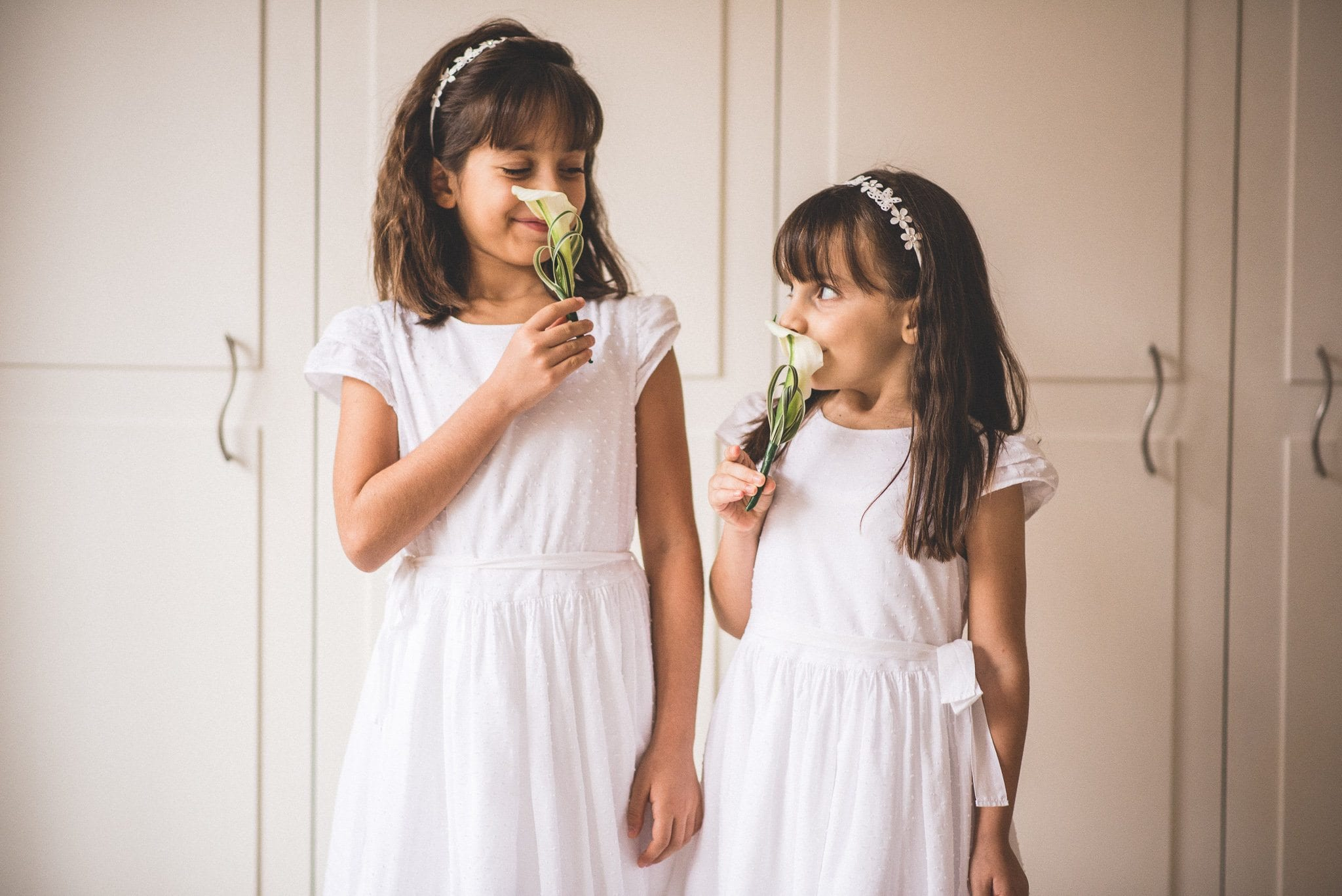 The two flower girls hold calla lilies up to their noses and grin at each other. They wear white shift dresses and silver headbands with flower details.