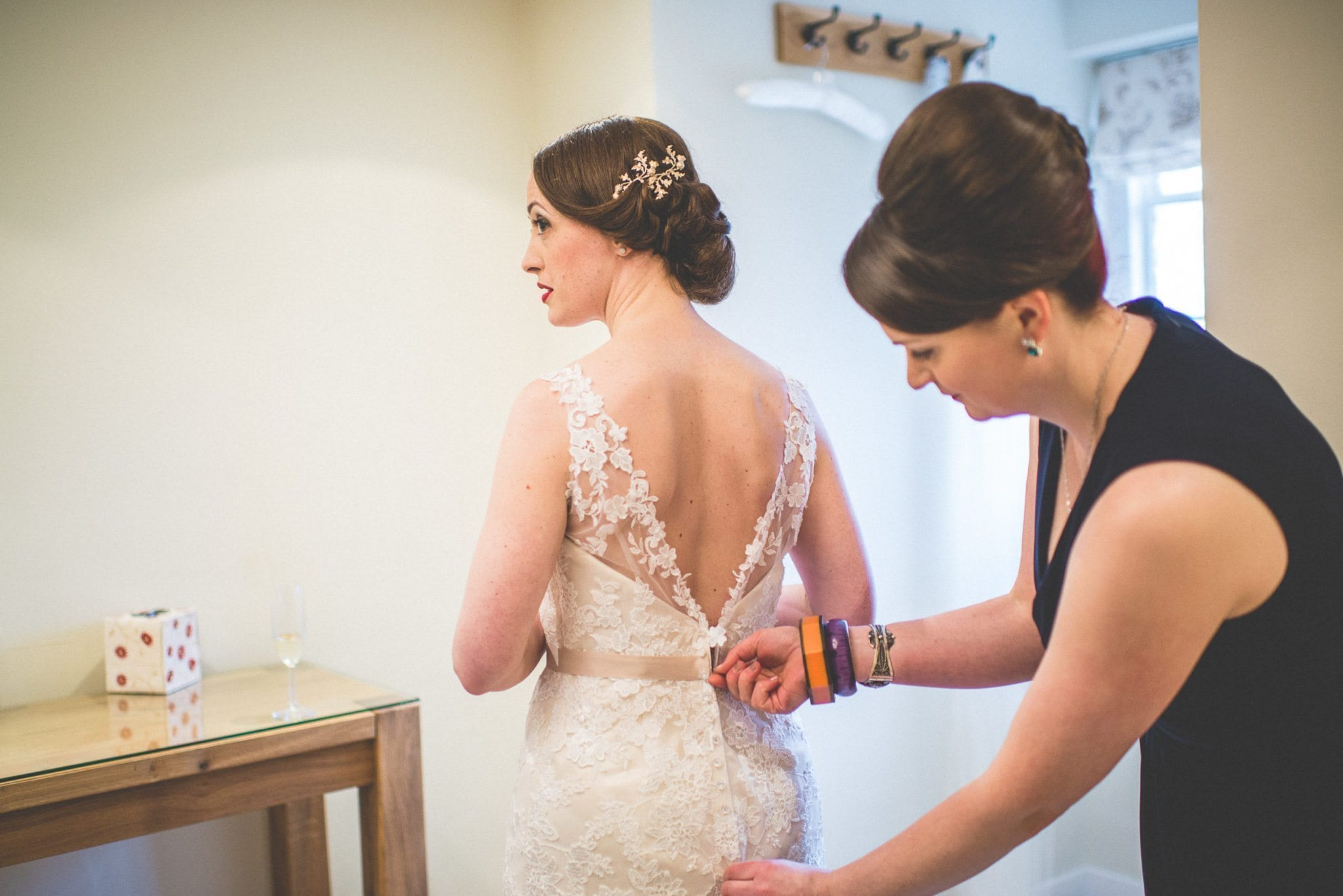 One of Jen's bridesmaids buttons her into her lace wedding gown with a deep V back