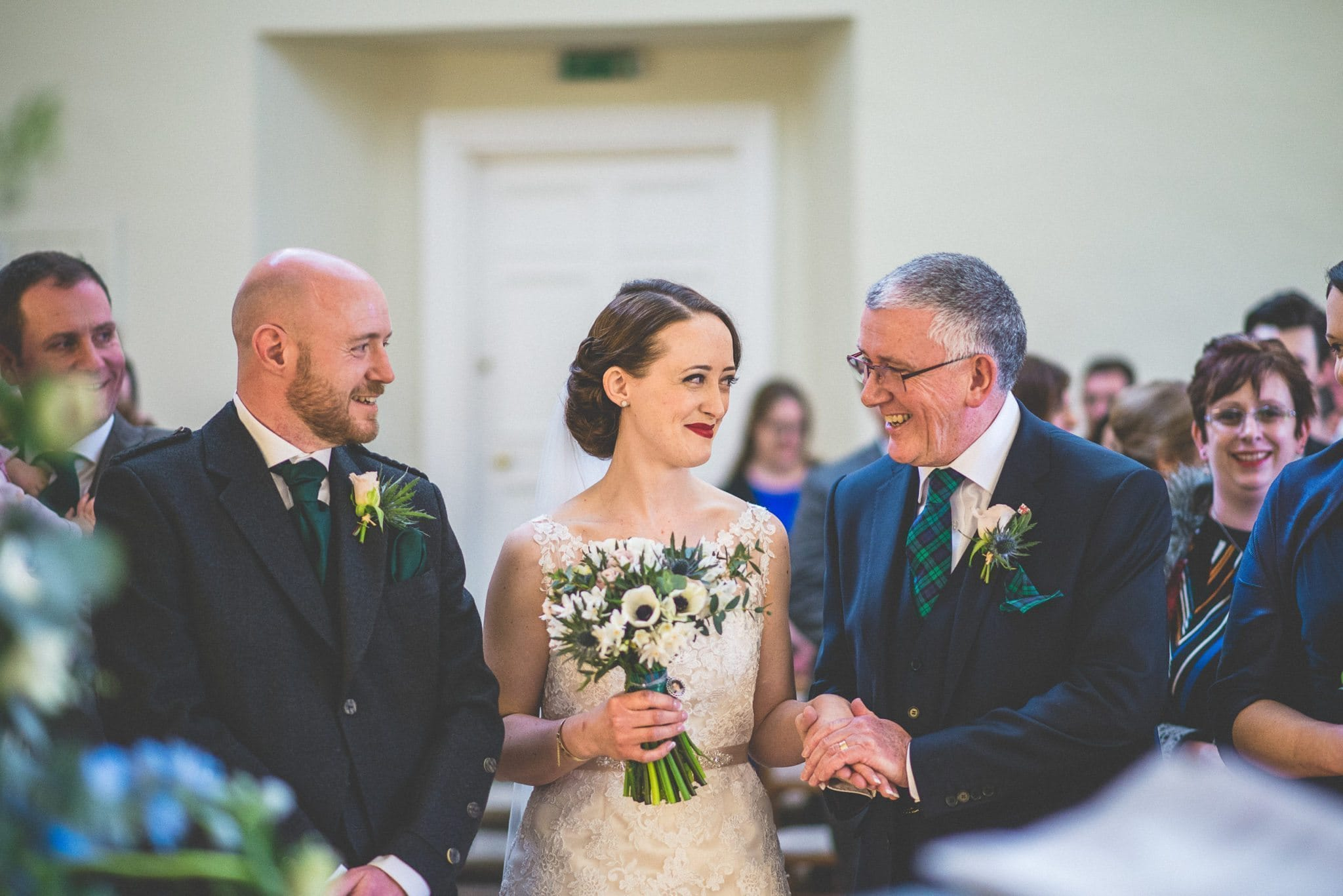 Brides smiles at her father as they reach the end of the aisle in Lantern Hall