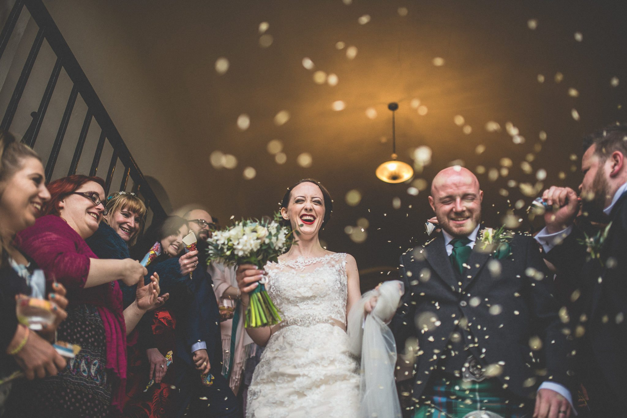 The bride and groom walk down the staircase in a shower of confetti at the Bishops Palace