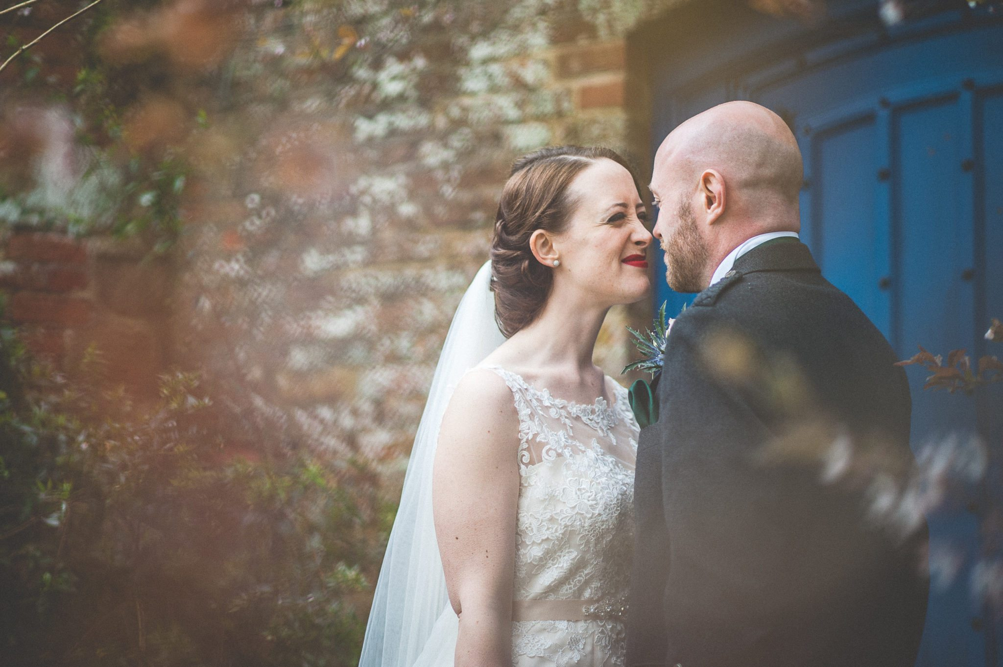 Bride and Groom smile at each other in front of a blue door at Farnham Castles Bishops Palace