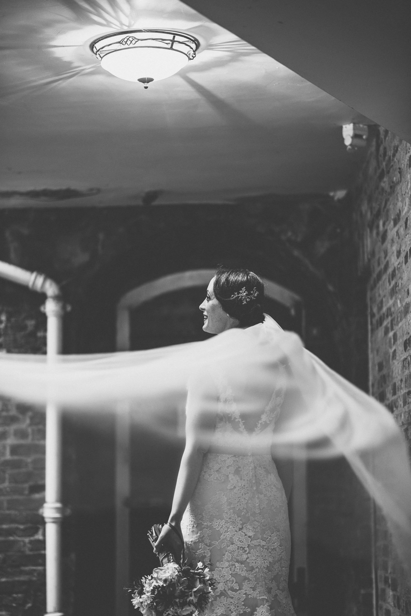 Black and White photo of the bride standing below a light with her bridal veil blowing in the wind