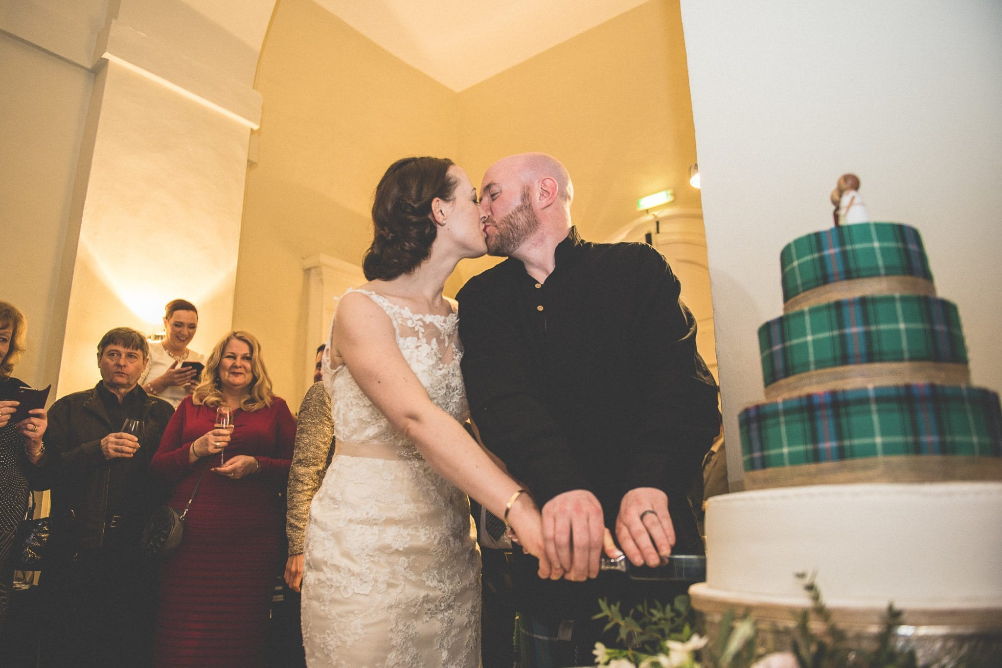 Bride and Groom cutting their scottish tartan cake at Farnham Castle