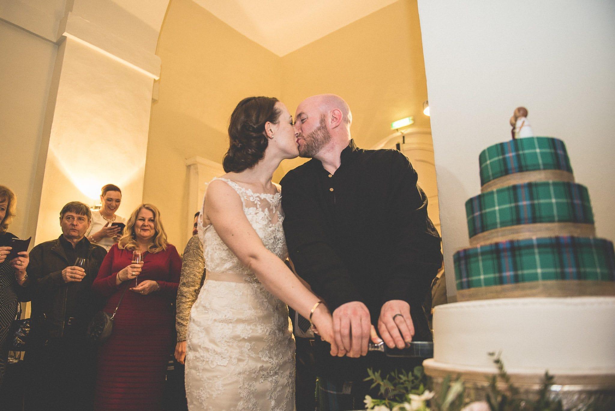 Bride and Groom cutting their scottish tartan cake at Farnham Castle