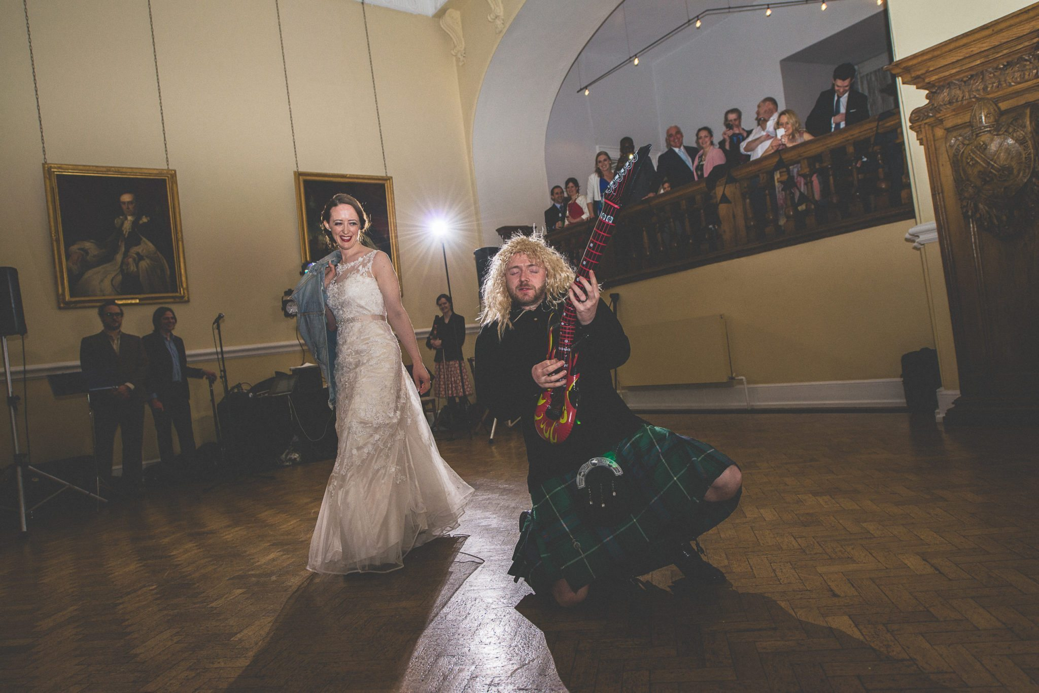 Scottish Groom in a long blond wig plays an inflatable guitar while his bride laughs