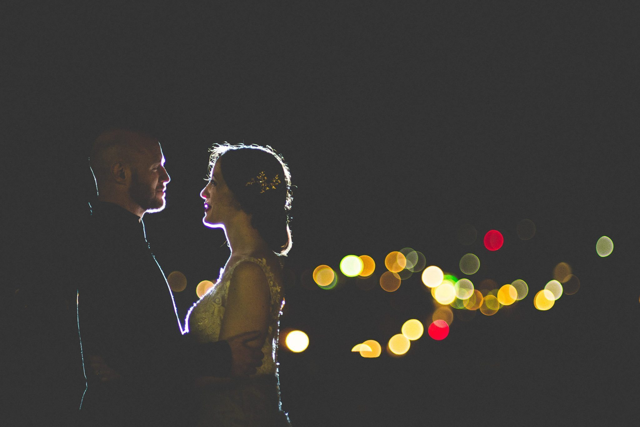 Backlit bride and groom smiling at each other at their Scottish Farnham Castle wedding