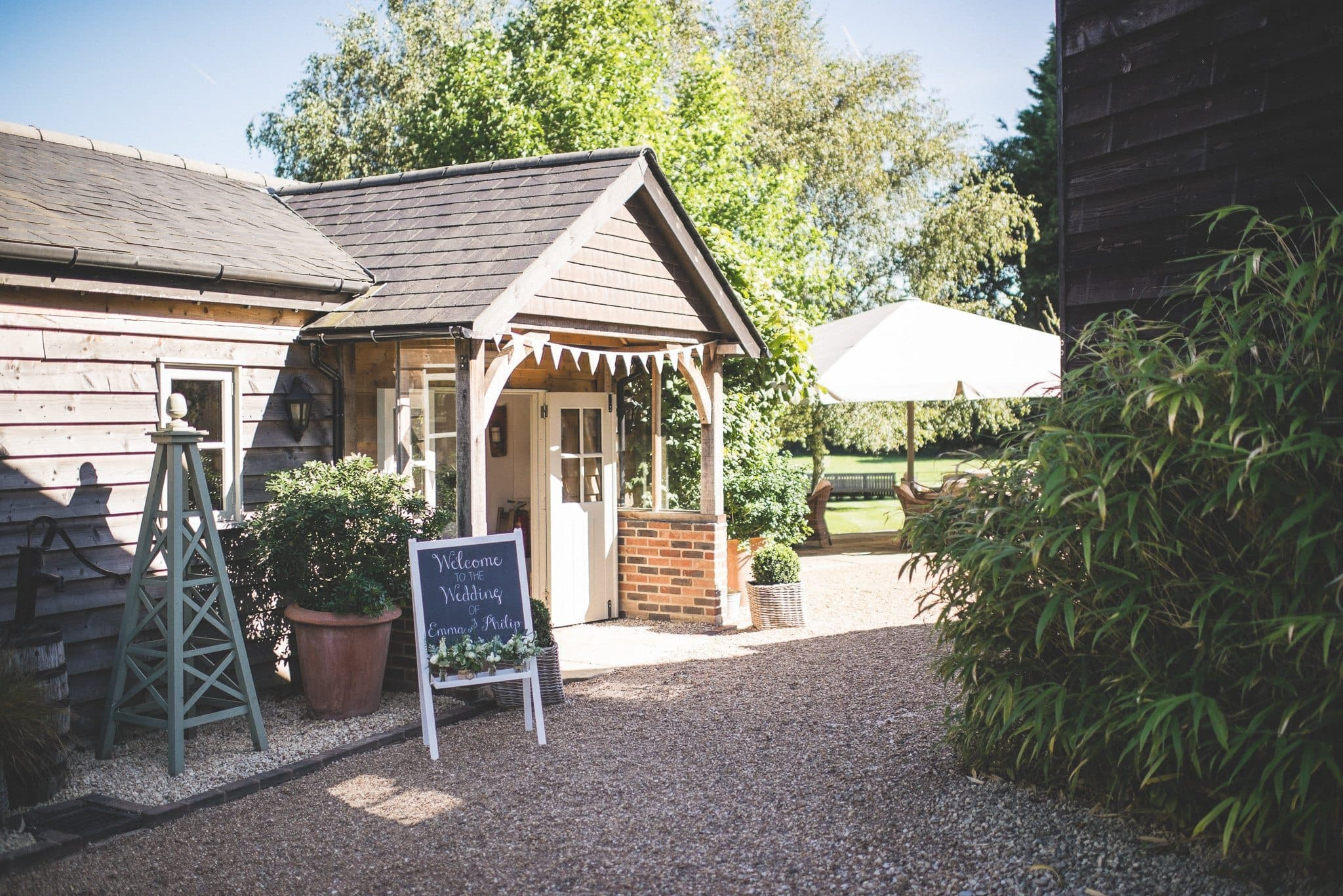 The entrance to the barn with bunting strung across it and a chalkboard welcome sign
