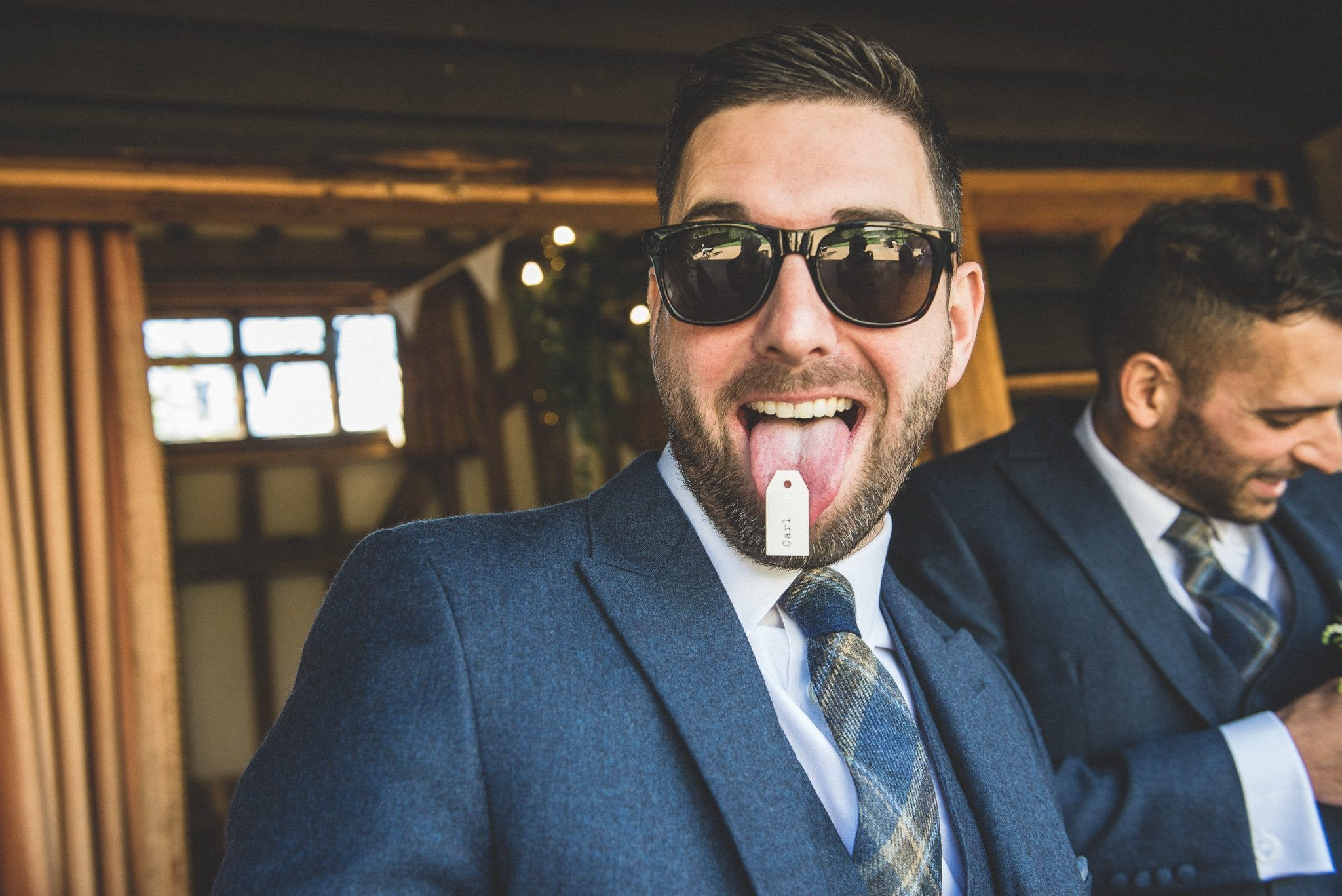 One of the groomsmen sticks his tongue out, showing a paper label attached to the end of it!