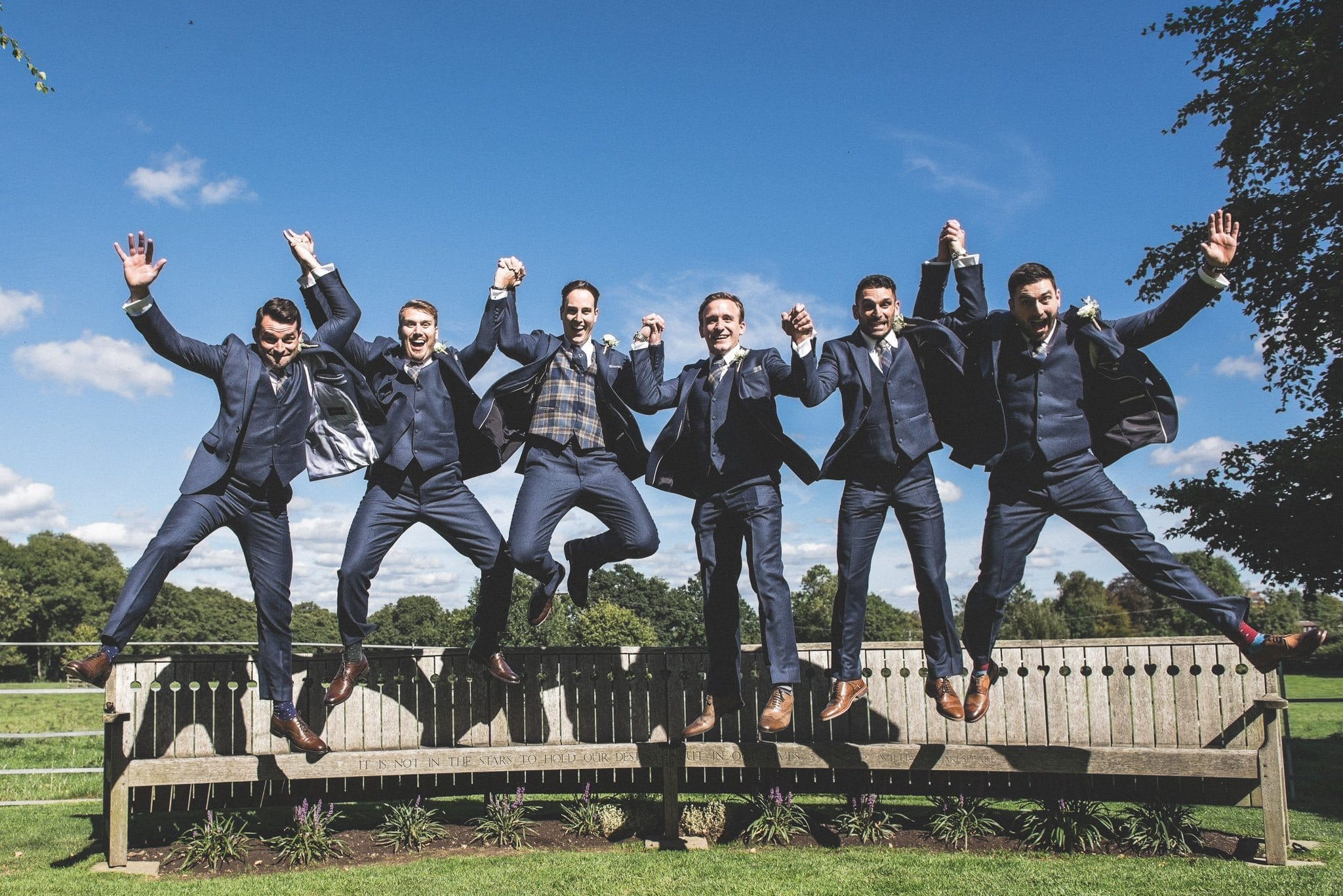 The groom and his groomsmen pictured in mid air as they jump off a bench