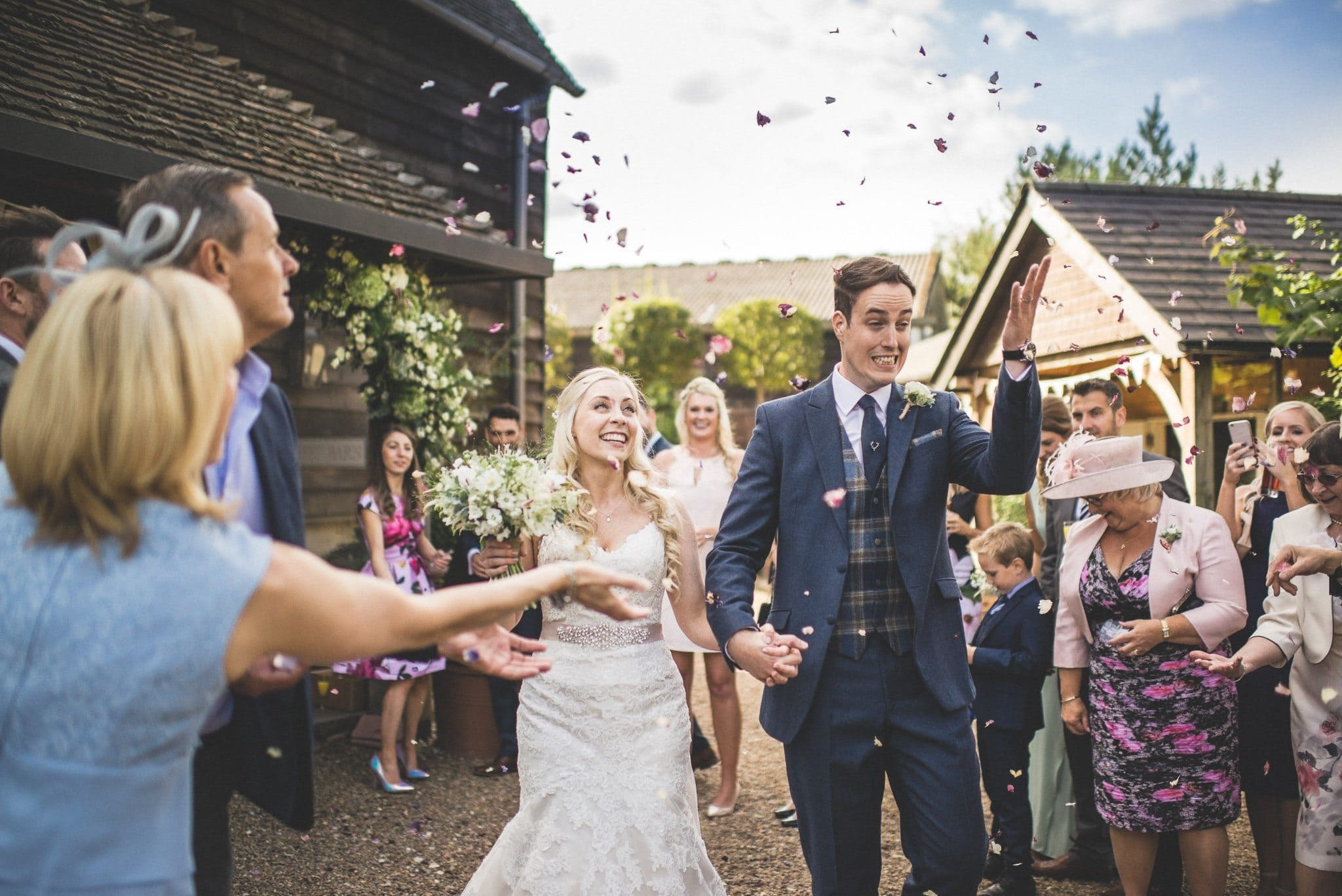 The couple walk through a shower of sweet pea petals as guests throw confetti