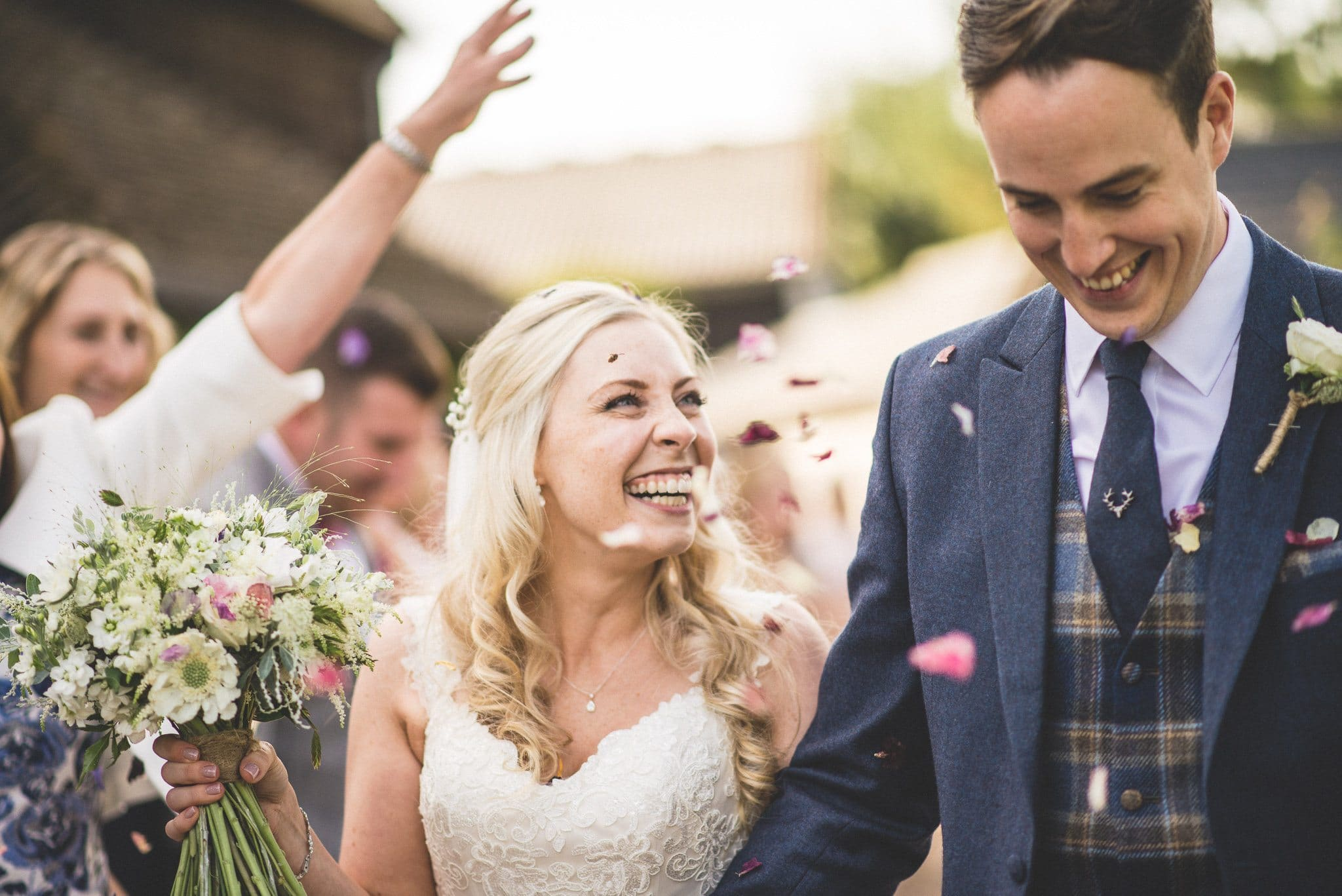 Emma looks at her groom and laughs as the confetti keeps on coming!