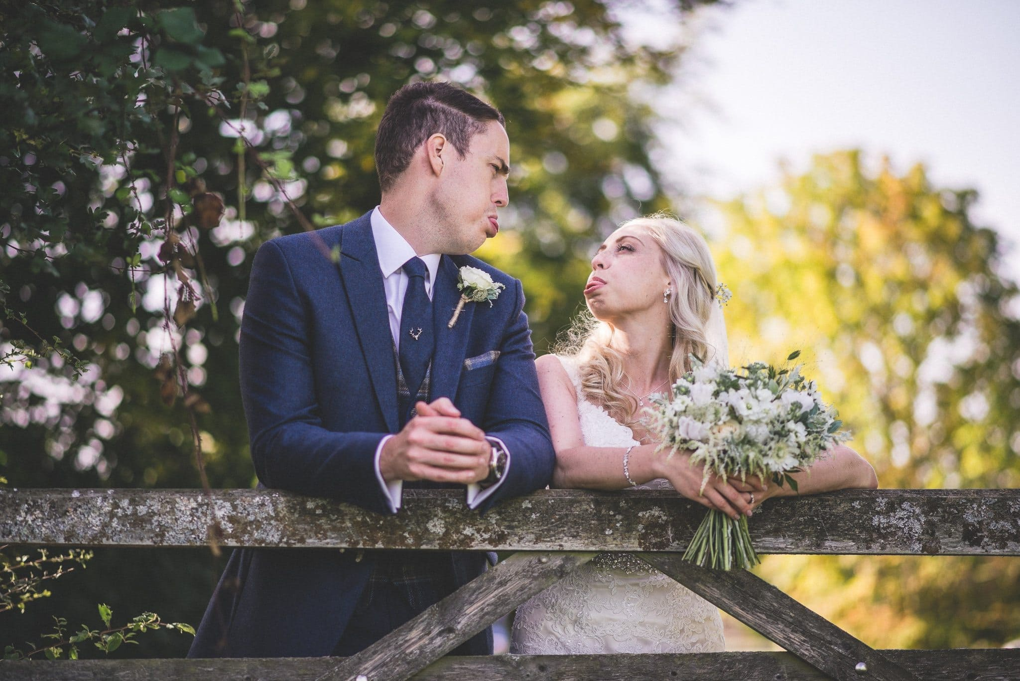 Emma and Phil blow raspberries at each other on their couple's shoot at their fun Gate Street Barn wedding