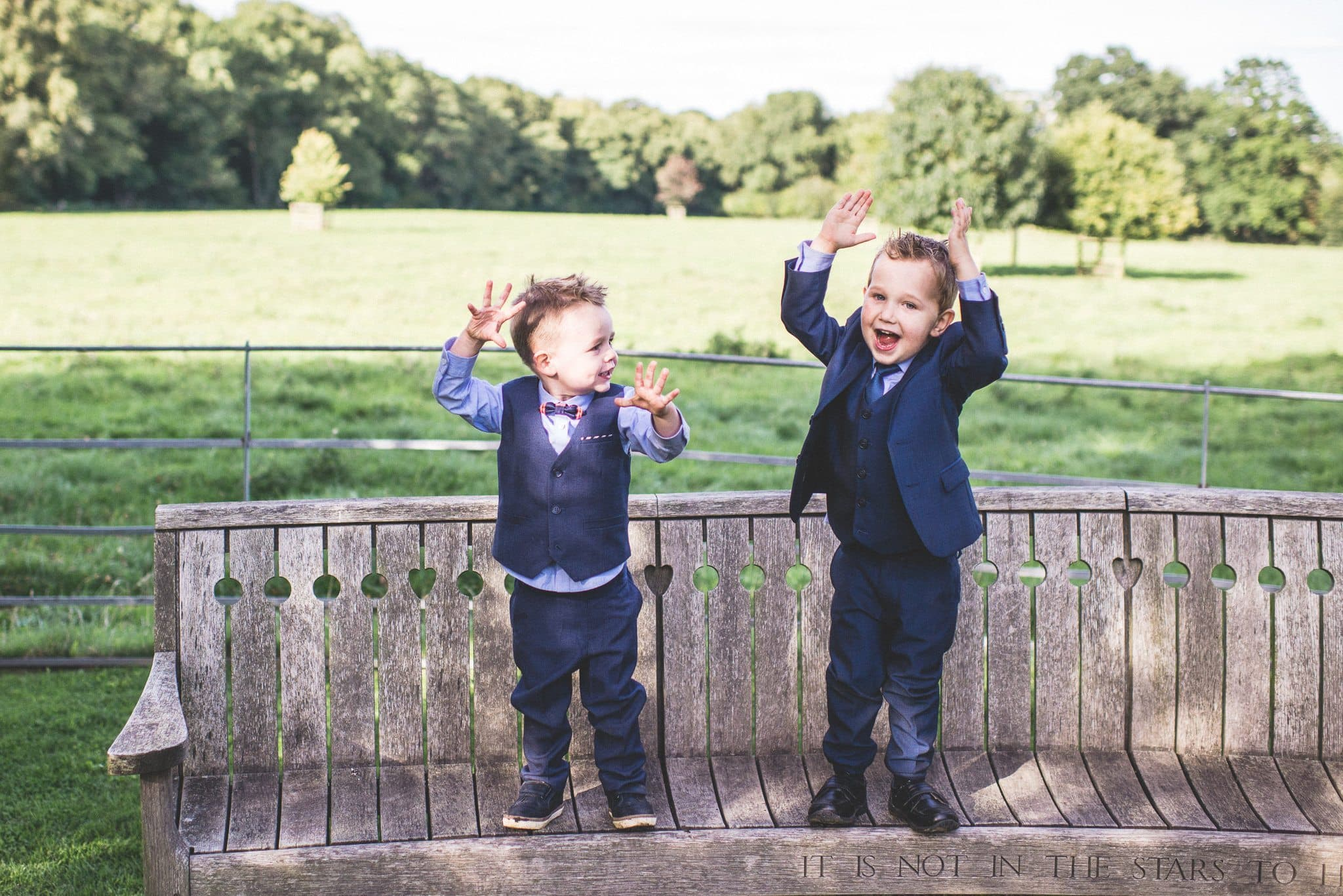 Two young boys looking v dapper in suits and waistcoats stand on a bench with their hands in the air.