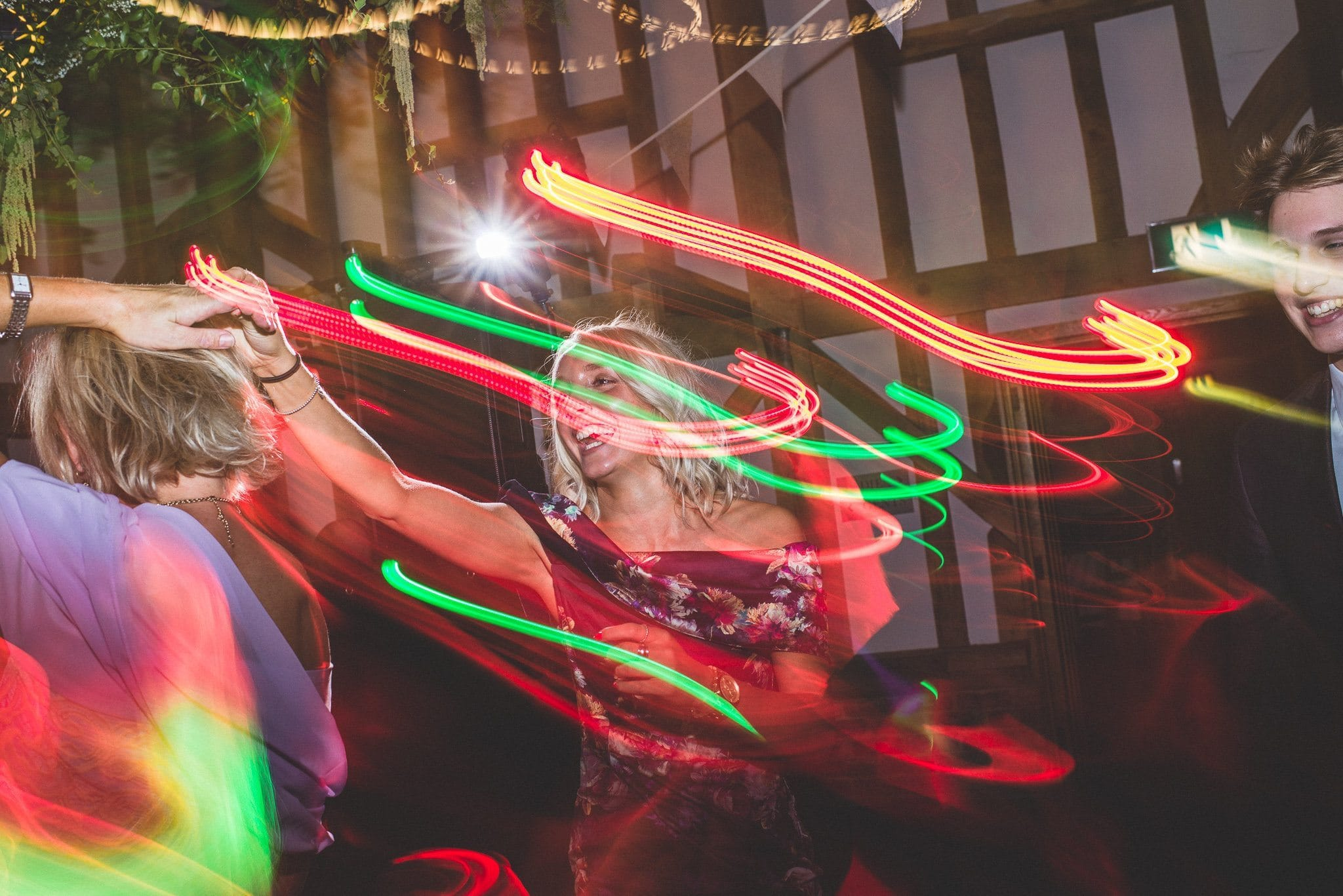 Green and orange light trails blur across the image as the dancefloor fills up. It looks like a great party!