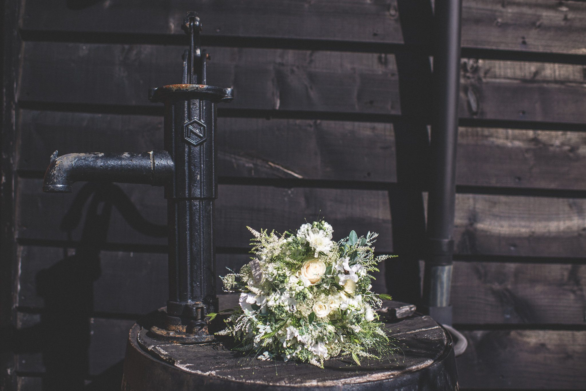 A close up of the bridal bouquet against a black clapboard wall. The bouquet features white and cream flowers, and lots of ferns and deep green foliage