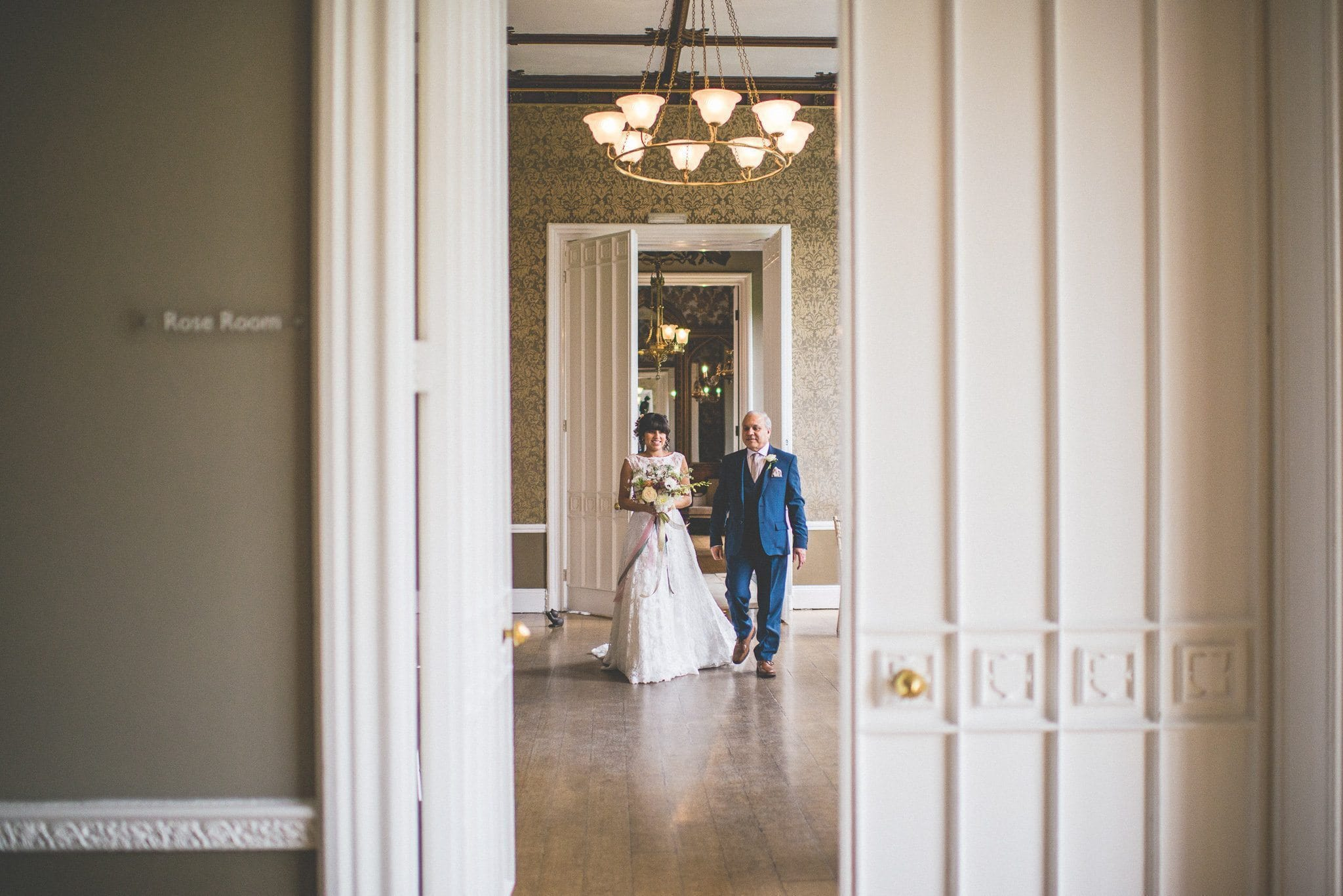 A shot through the door as bride Jasmin crosses to enter the ceremony room with her father. She wears a lace dress and carries a bouquet tied with colourful ribbons