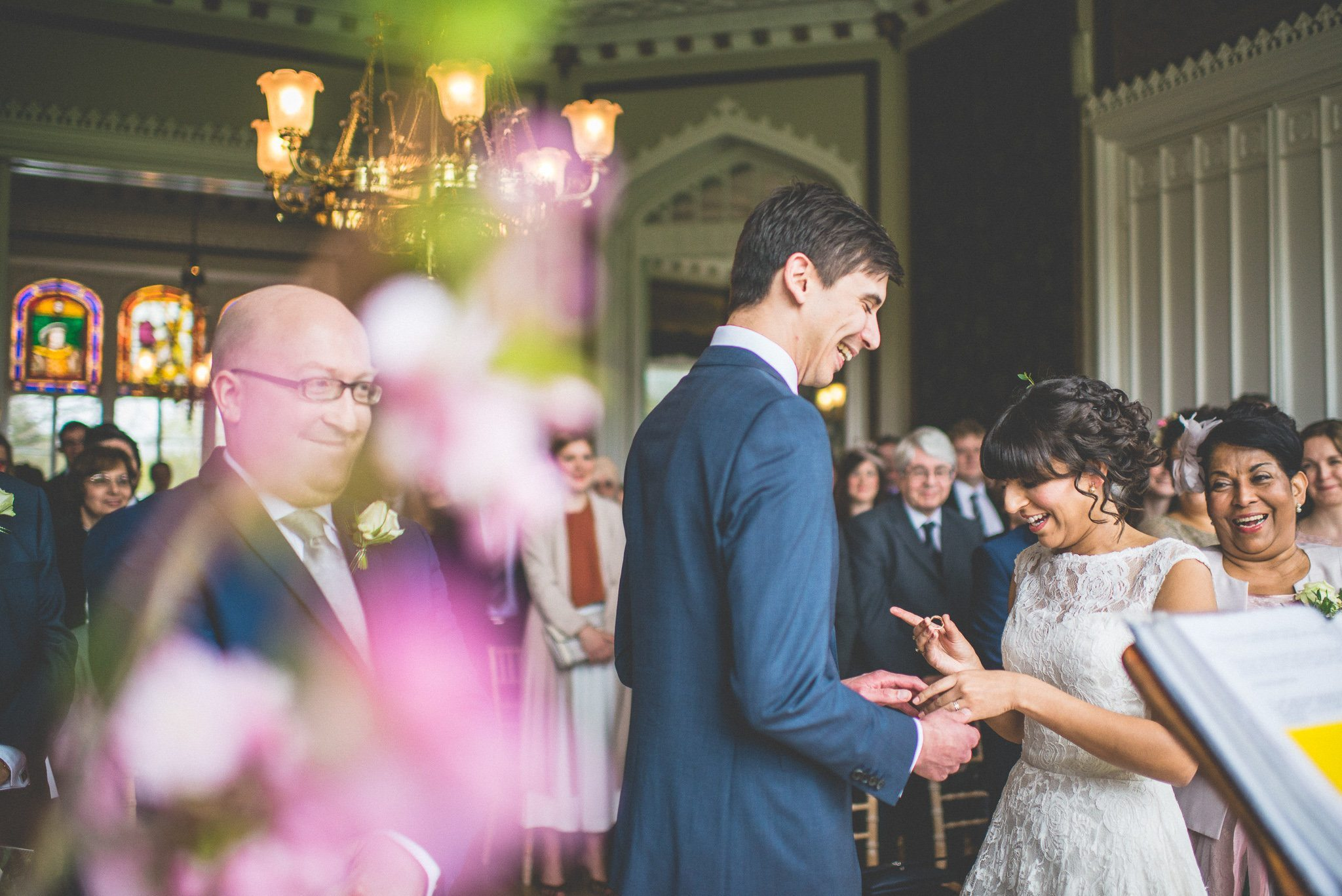 The couple and the congregation laugh, as Jasmin puts a ring on Andy's finger. A pink floral arrangement is in soft focus in the foreground.