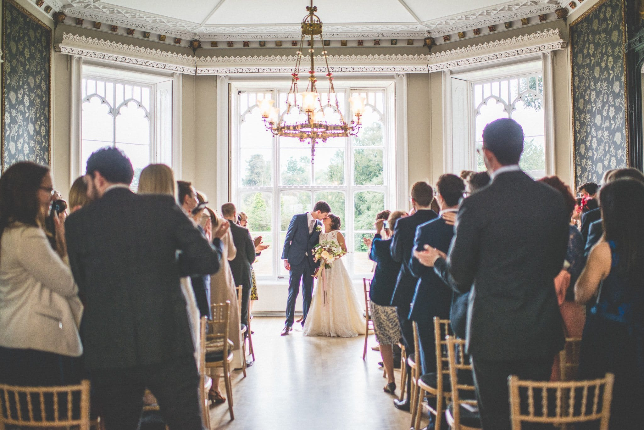 The newly married Andy and Jasmin kiss in front of the floor to ceiling windows of the ceremony room, while their guests stand and applaud