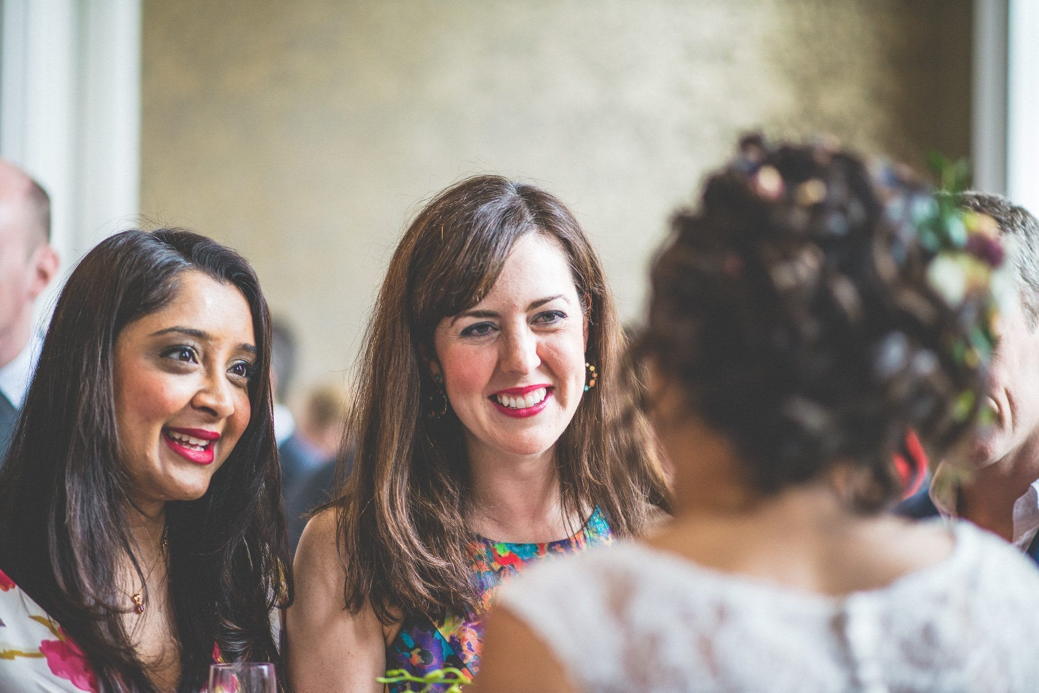 Two guests in bright floral dresses chat to the bride