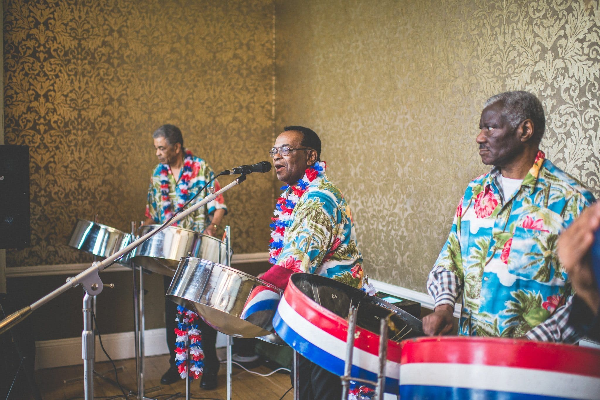 A steel band plays, wearing Hawaiian shirts and red, white and blue flower garlands