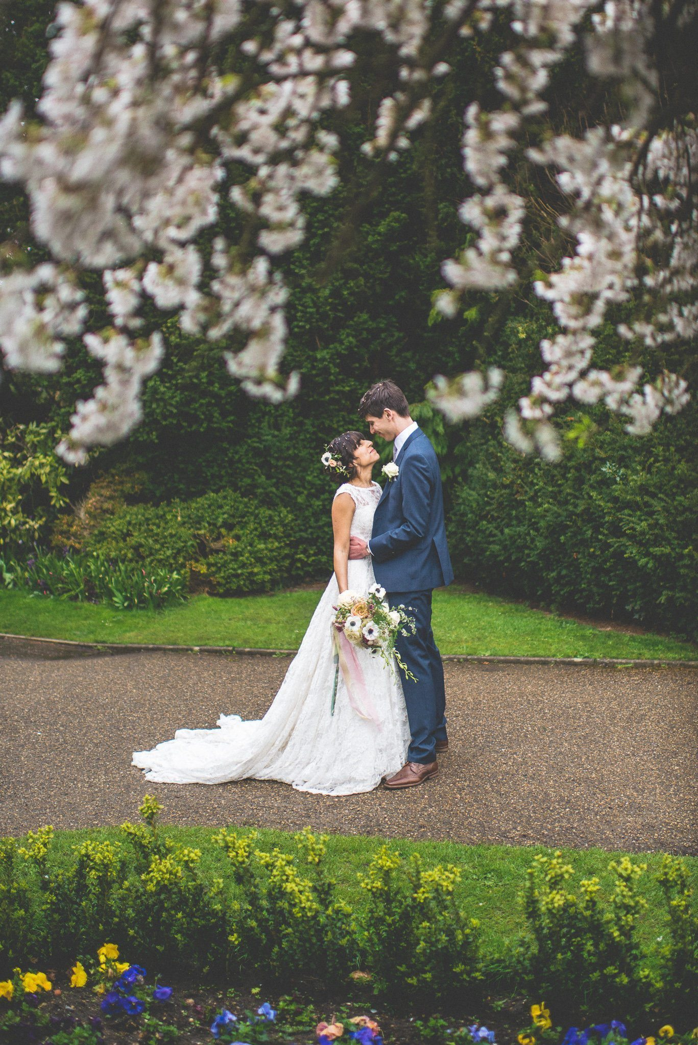 Bride and Groom standing among spring blossom at Nonsuch Mansion
