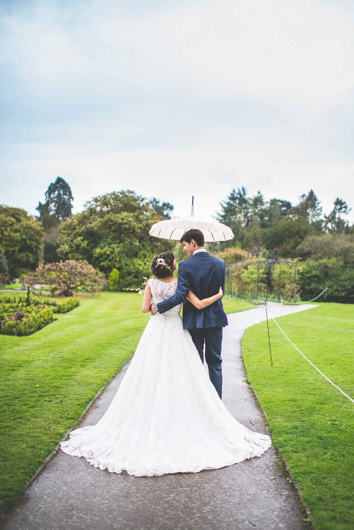 The couple walk down a path in the grounds of Nonsuch Mansion. Jasmin's dress spreads out behind her in a lace train, and Andy holds a white parasol over their heads