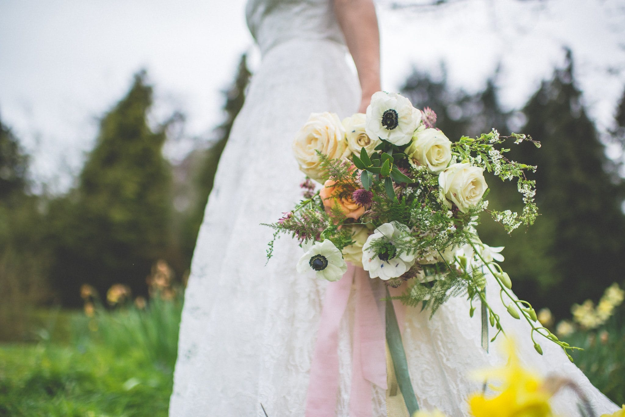 A shot looking up from the ground, and focusing on the bridal bouquet of anemones and roses, tied with pale pink, sage green and peach silk ribbon
