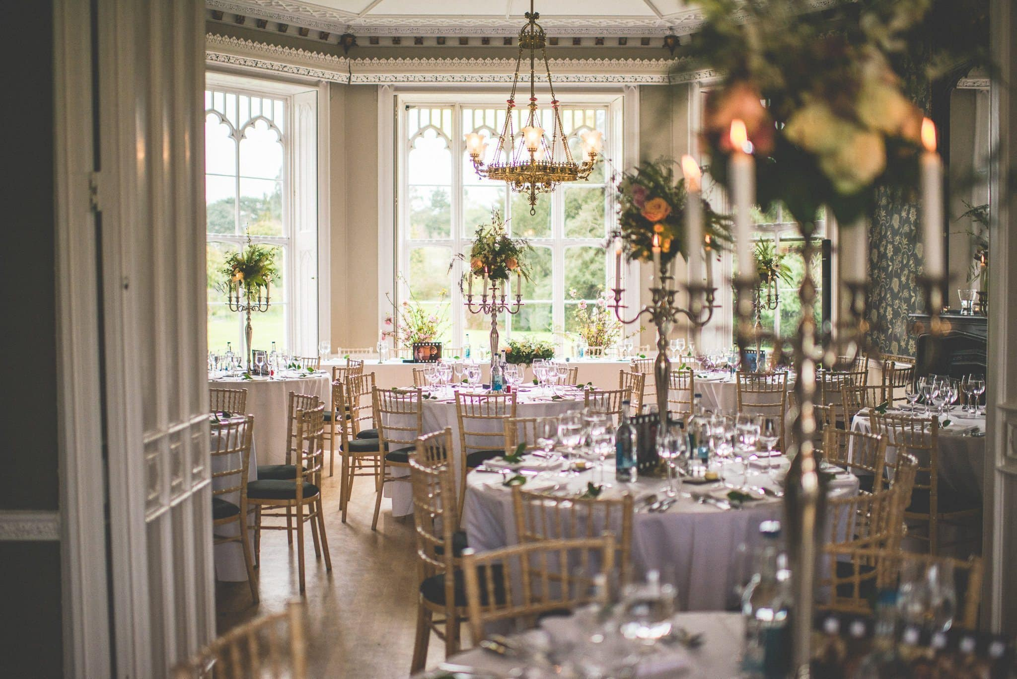 A shot through the door of the reception room showing the round tables decorated with candelabras and tall peach and cream floral arrangements