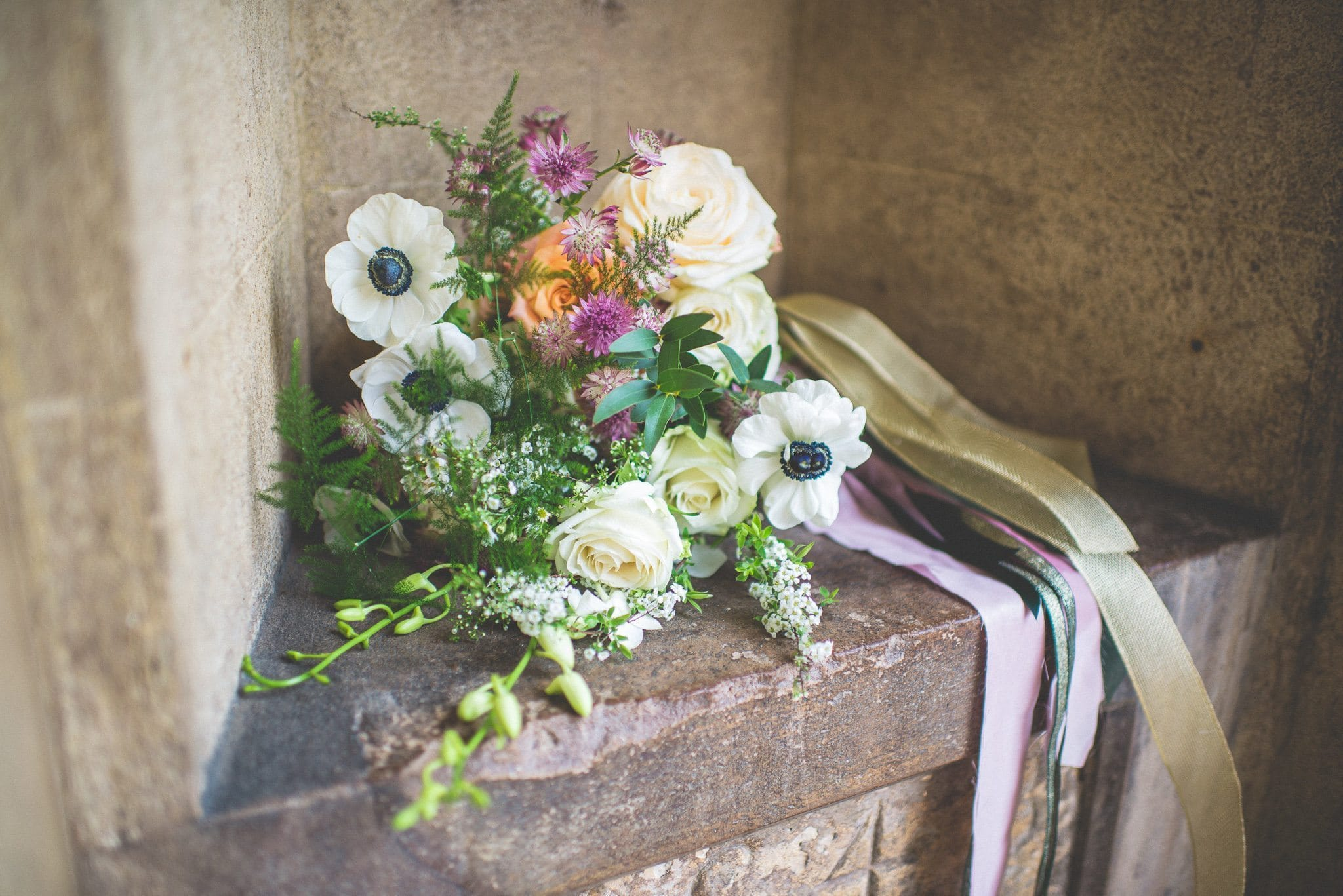 Jasmin's bridal bouquet - featuring anemones and cream and orange roses, and tied with colourful silk ribbon