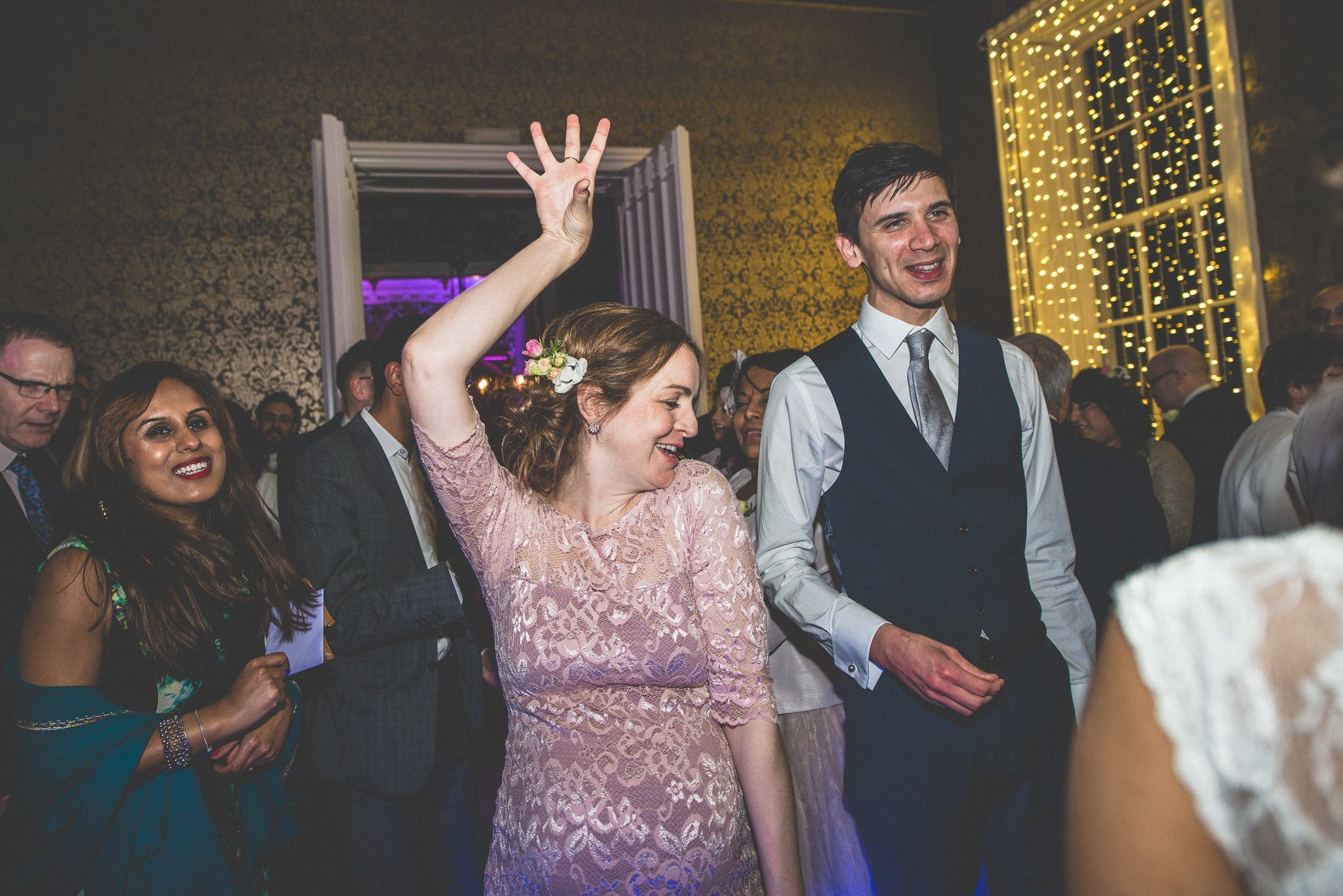 A heavily pregnant bridesmaid in a pink lace dress rocks out on the dancefloor