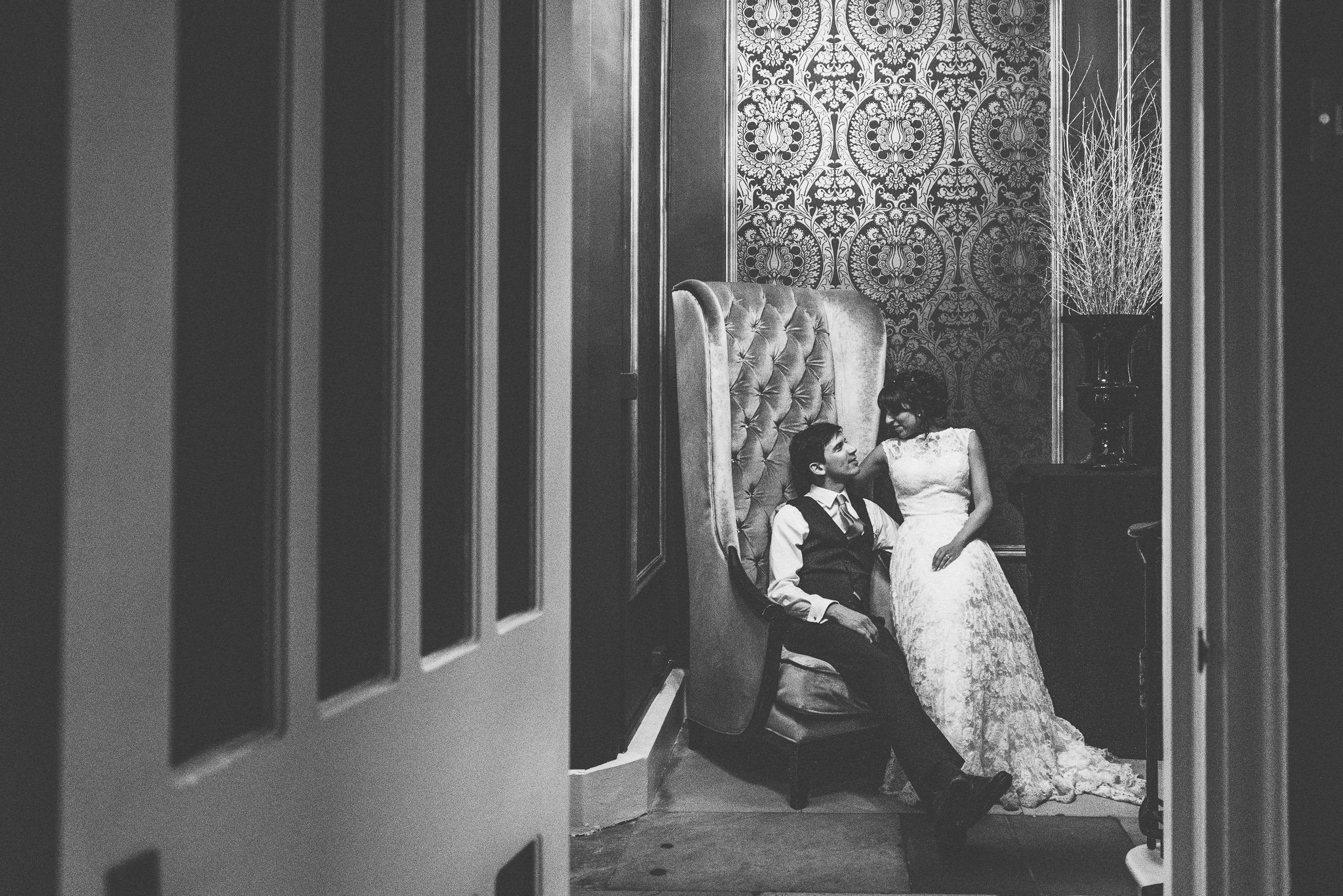 A black and white shot of the couple sitting together and relaxing in a high backed armchair at the end of the night