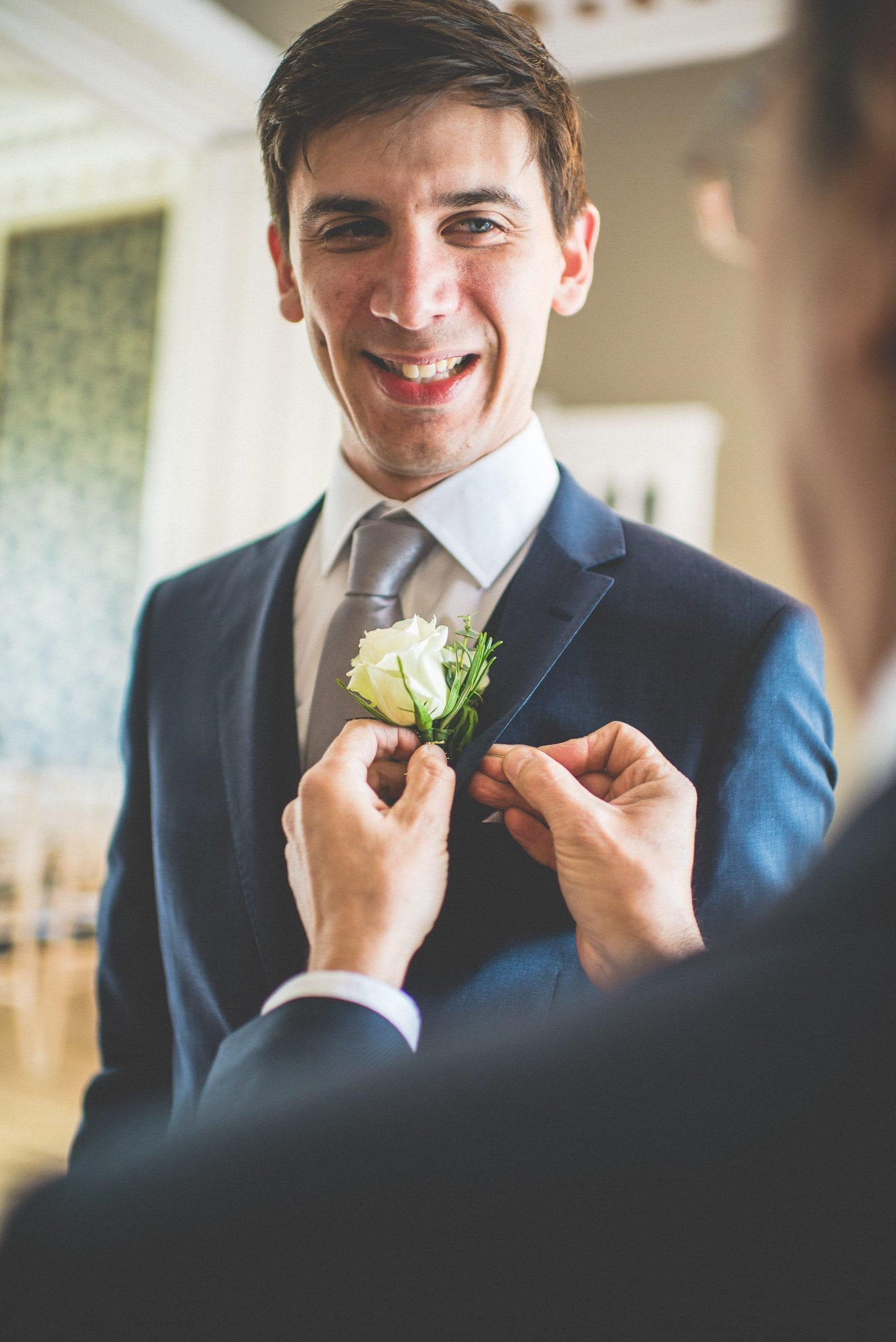 A groomsman fastens Andy's buttonhole to his navy suit