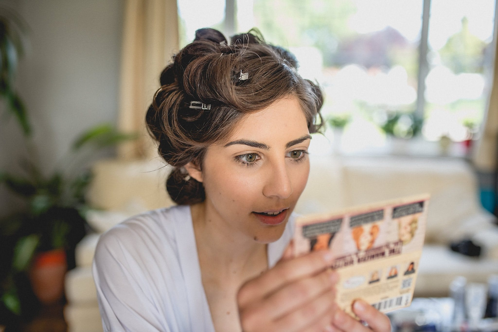 A bride with clips in her hair checks out her makeup as she gets ready for her London wedding
