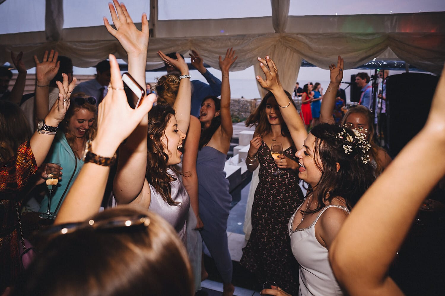 Bride dancing with her friends with their hands up in her wedding marquee