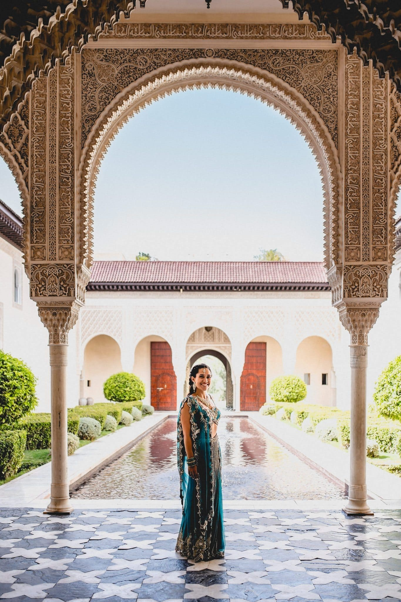 Indian bride standing under the Moroccan arches at Ksar Char Bagh in Marrakech