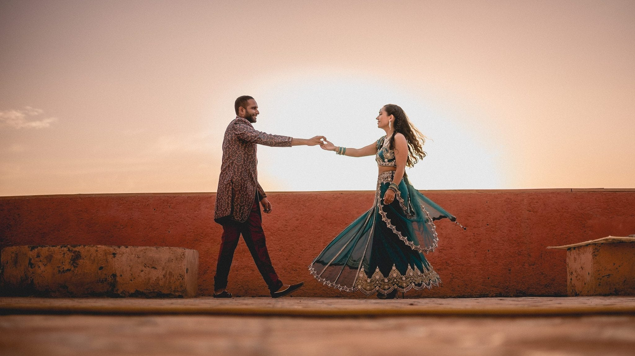 Indian couple dance on a rooftop as the sun sets in Marrakech