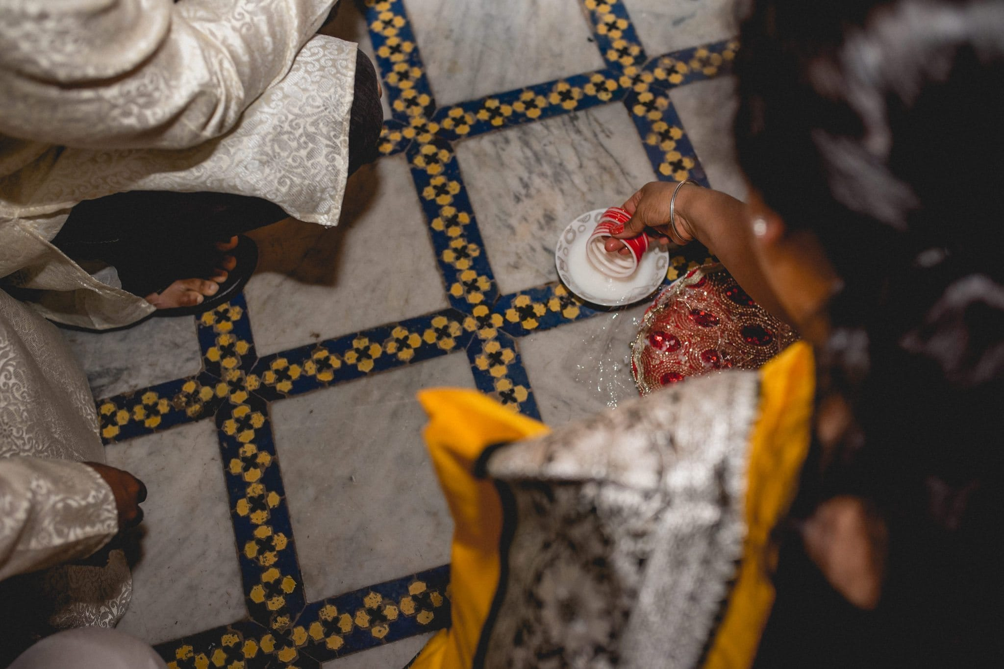 Indian woman washing red wedding bracelets in milk at a Morocco destination wedding
