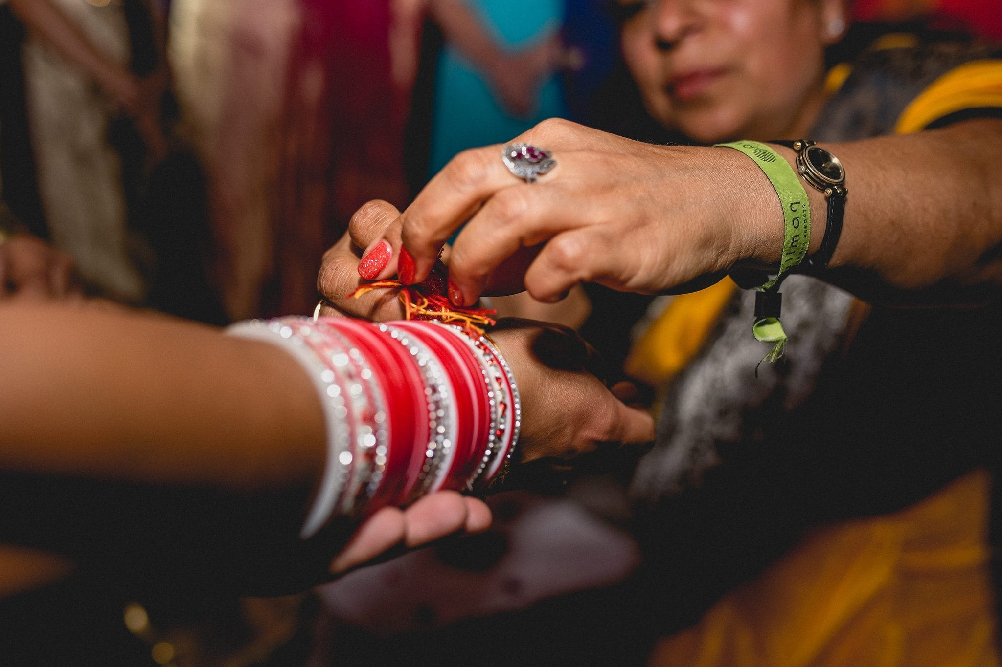 Red thread is tied around the bride's wrist during the Hindu part of the ceremony