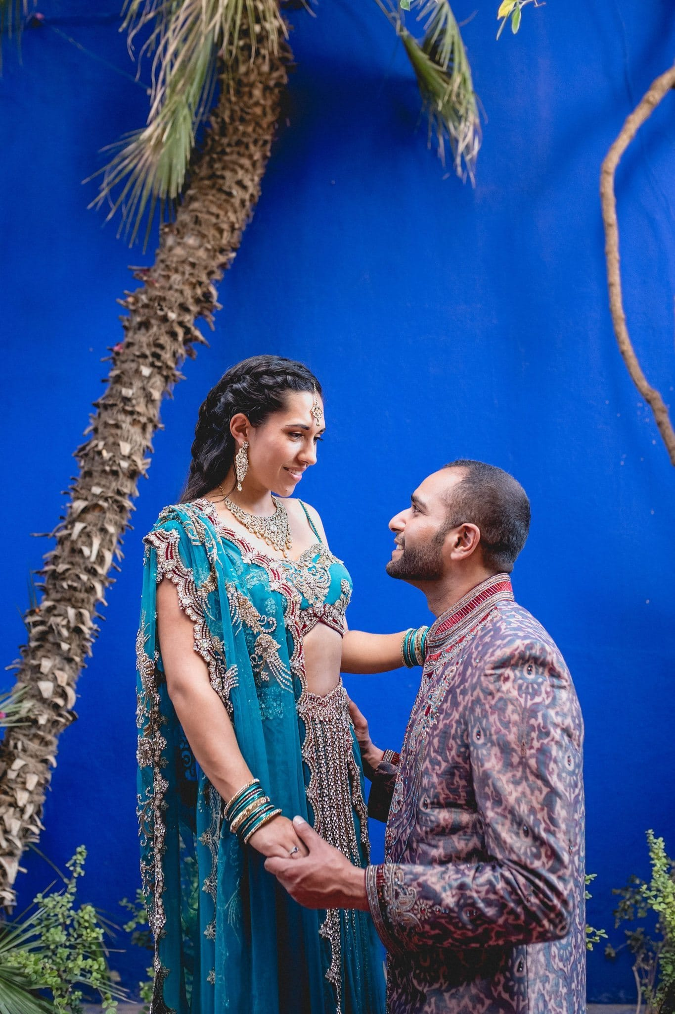 Asian bride and groom stand against the iconic blue walls of the Majorelle Gardens