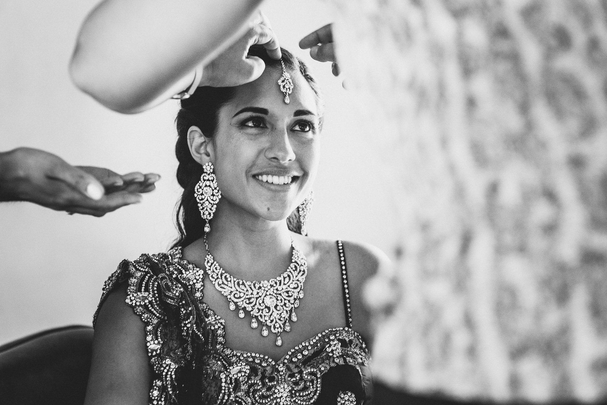 A black and white shot of Indian bride getting ready for her Marrakech destination wedding. She wears elaborate earrings and a necklace, and jewellery is being positioned on her forehead as she smiles.