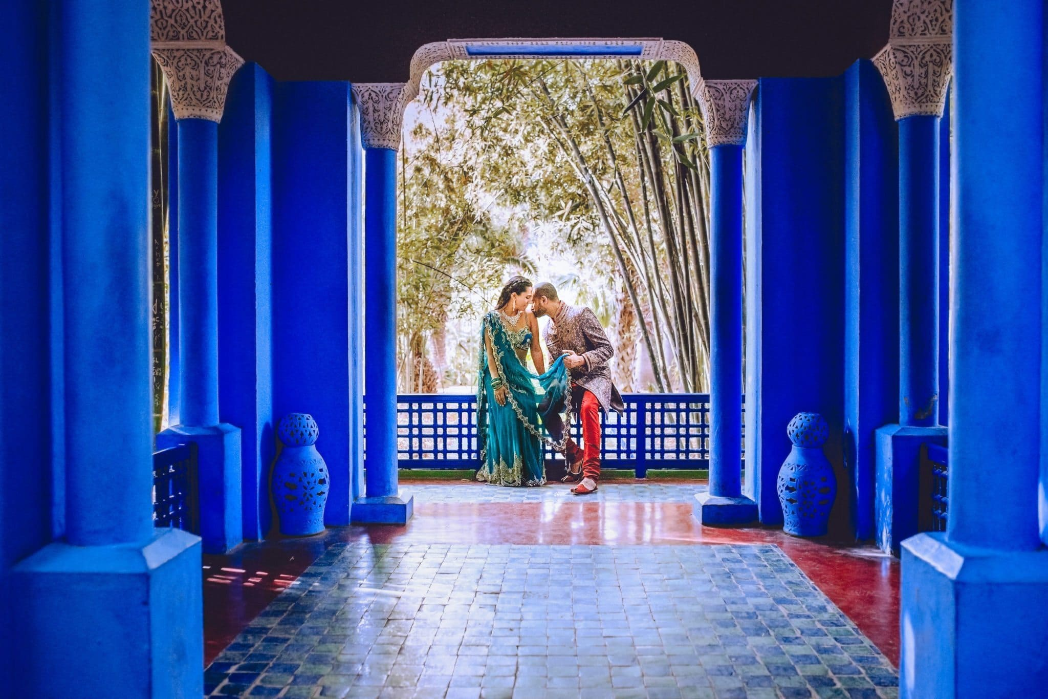 Indian groom kissing his bride's shoulders overlooking the Marrakech Majorelle Gardens