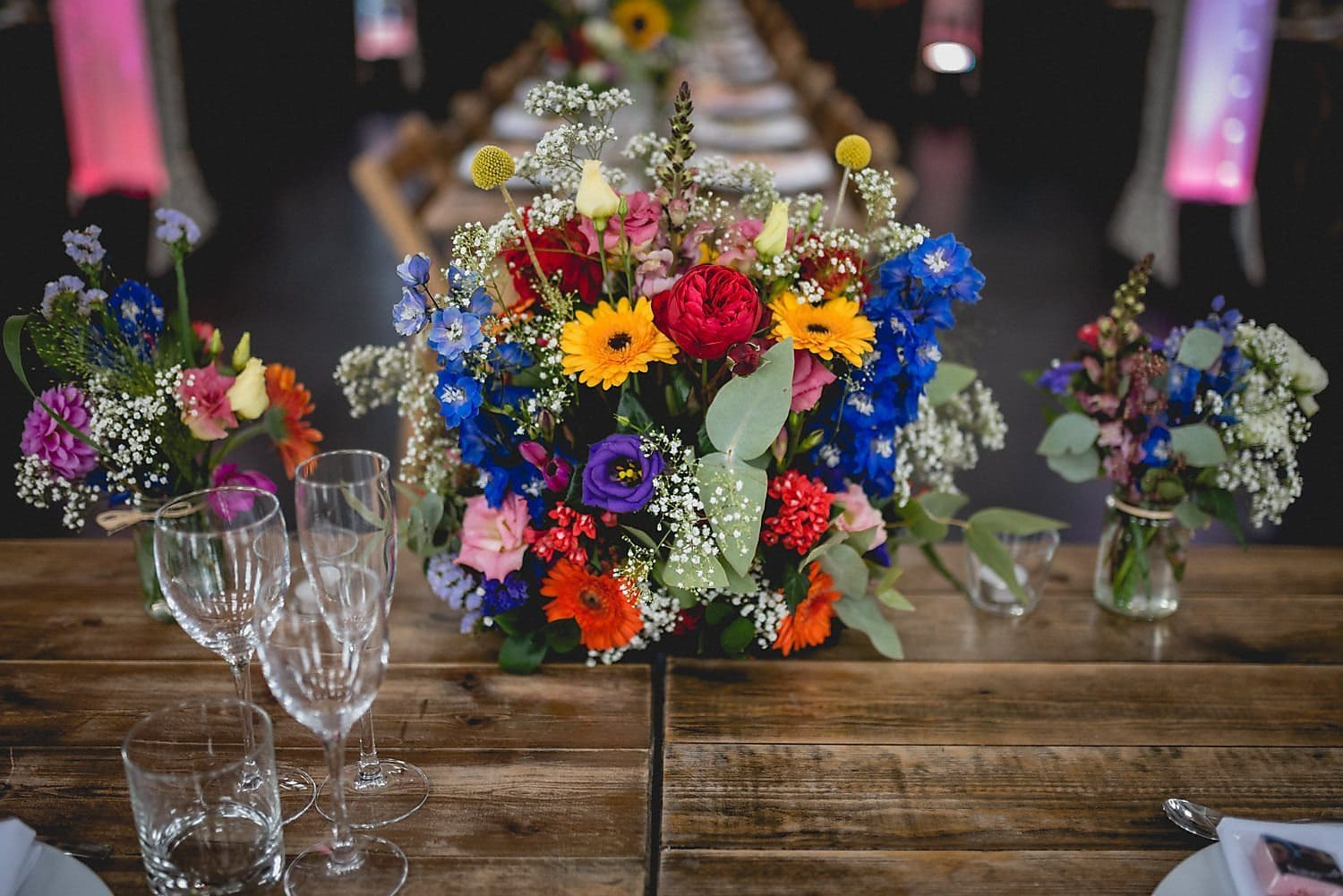 The top table flowers at a colourful West Reservoir Centre wedding. The flowers include gerberas, gypsophila and craspedia