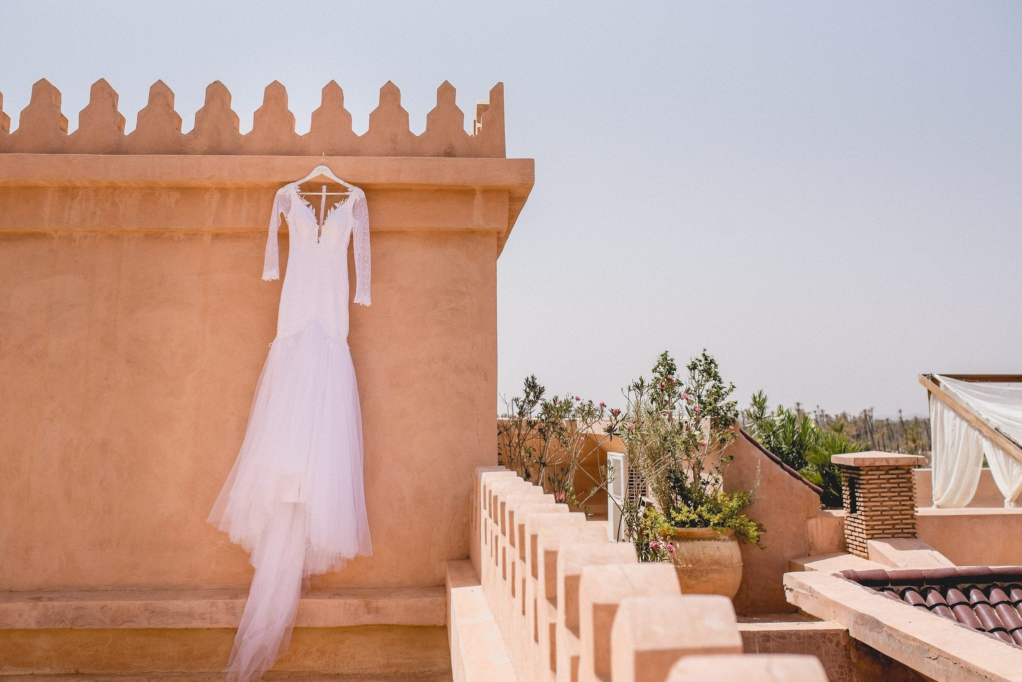 Luxury Marrakech destination wedding gown hangs on the roof terrace of Ksar Char Bagh