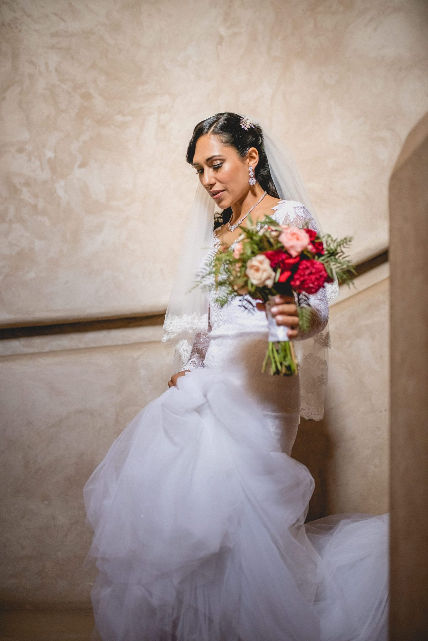 Aaysha descends the stairs in her dress and veil, holding a bouquet of red and peach flowers.