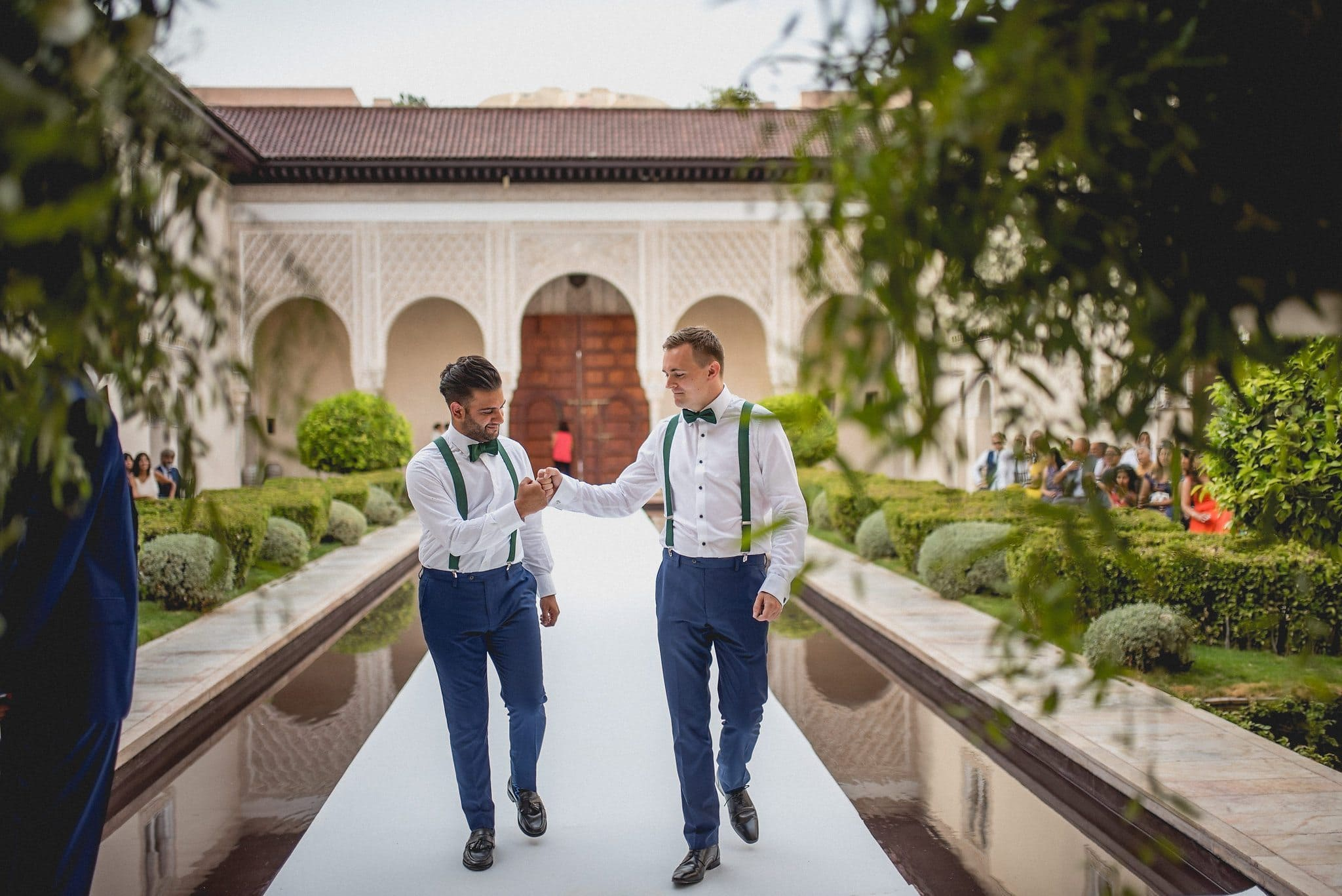 Two of the groomsmen fist bump as they reach the end of the aisle