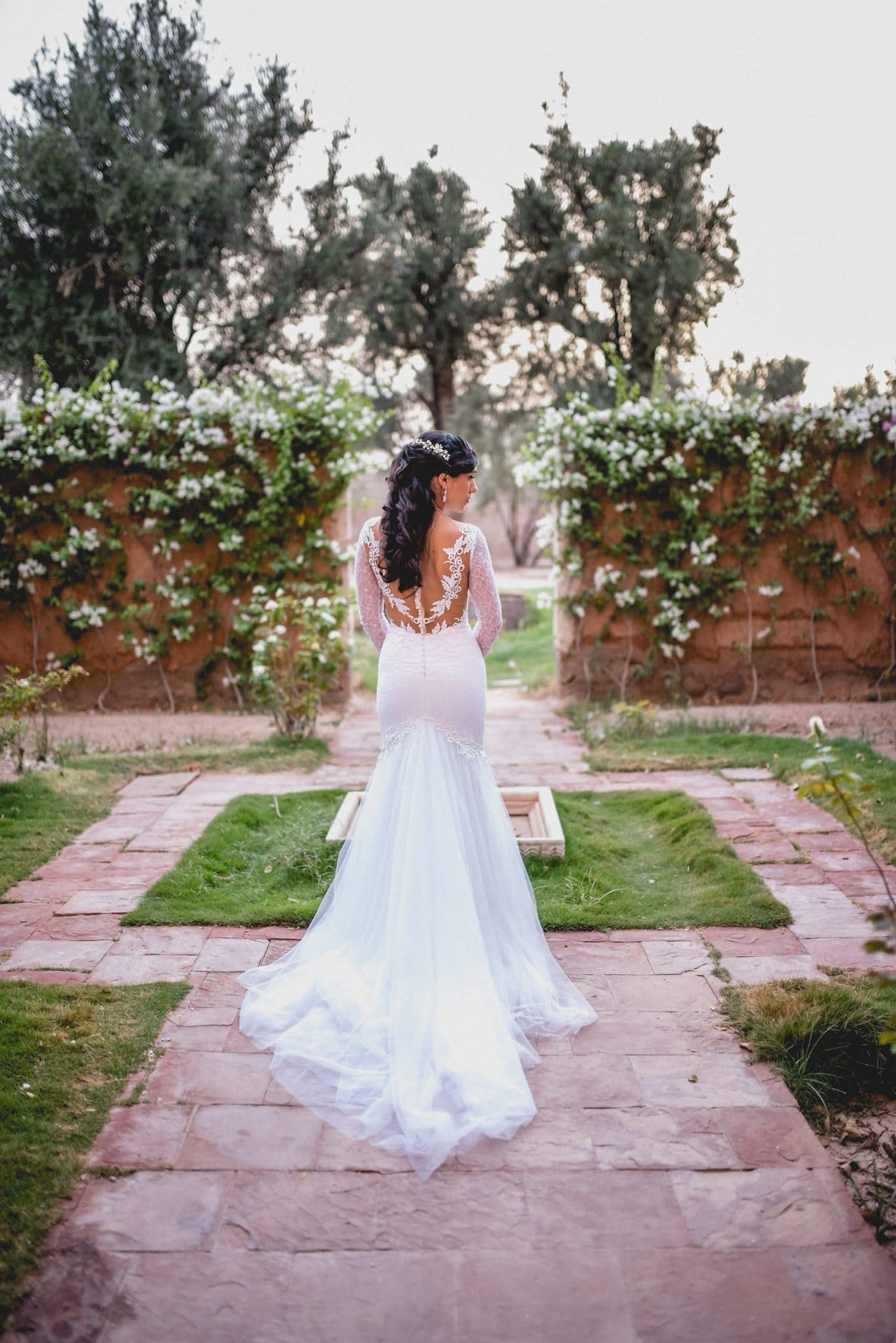A bridal portrait. She turns to face the camera in the walled garden at Ksar Char Bagh luxury hotel in Marrakech