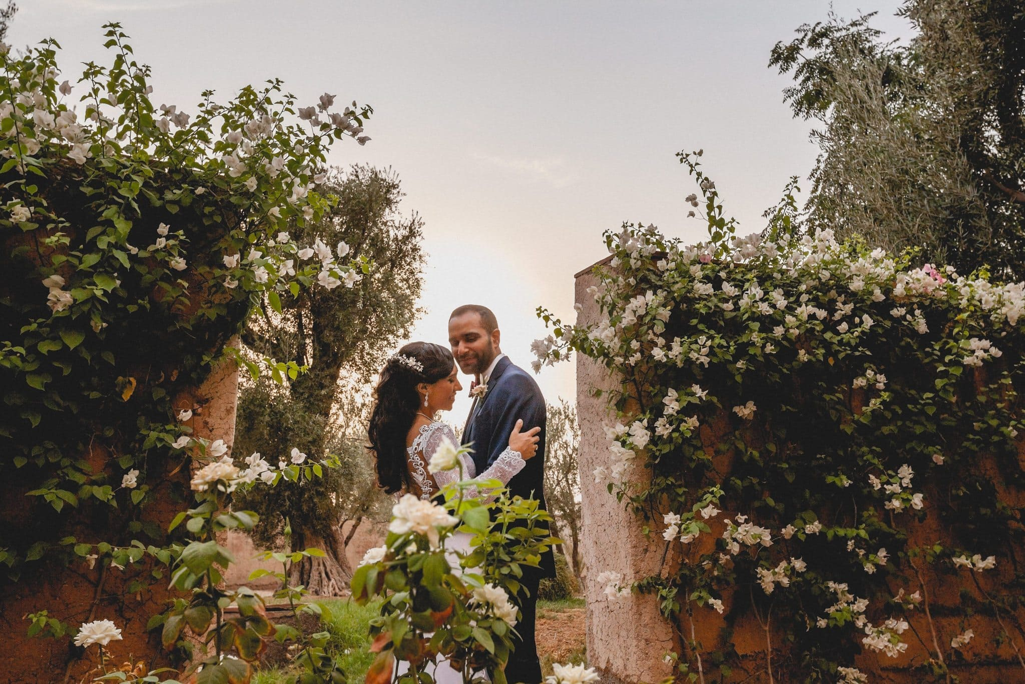The bride and groom cuddle in the rose garden at their Ksar Char Bagh Luxury Marrakech Destination Wedding